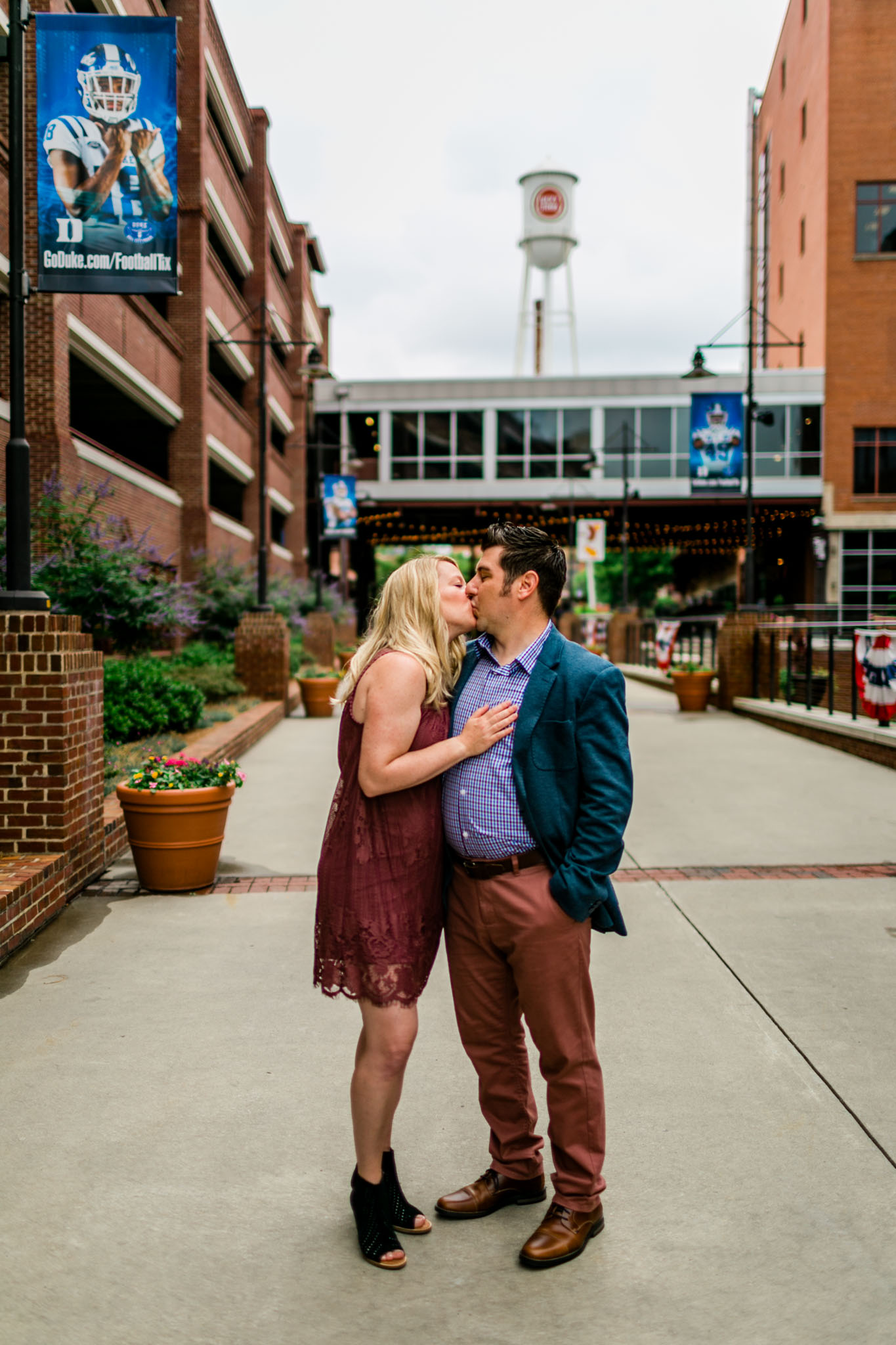 Durham Family Photographer | By G. Lin Photography | Portrait of couple kissing at American Tobacco Camups