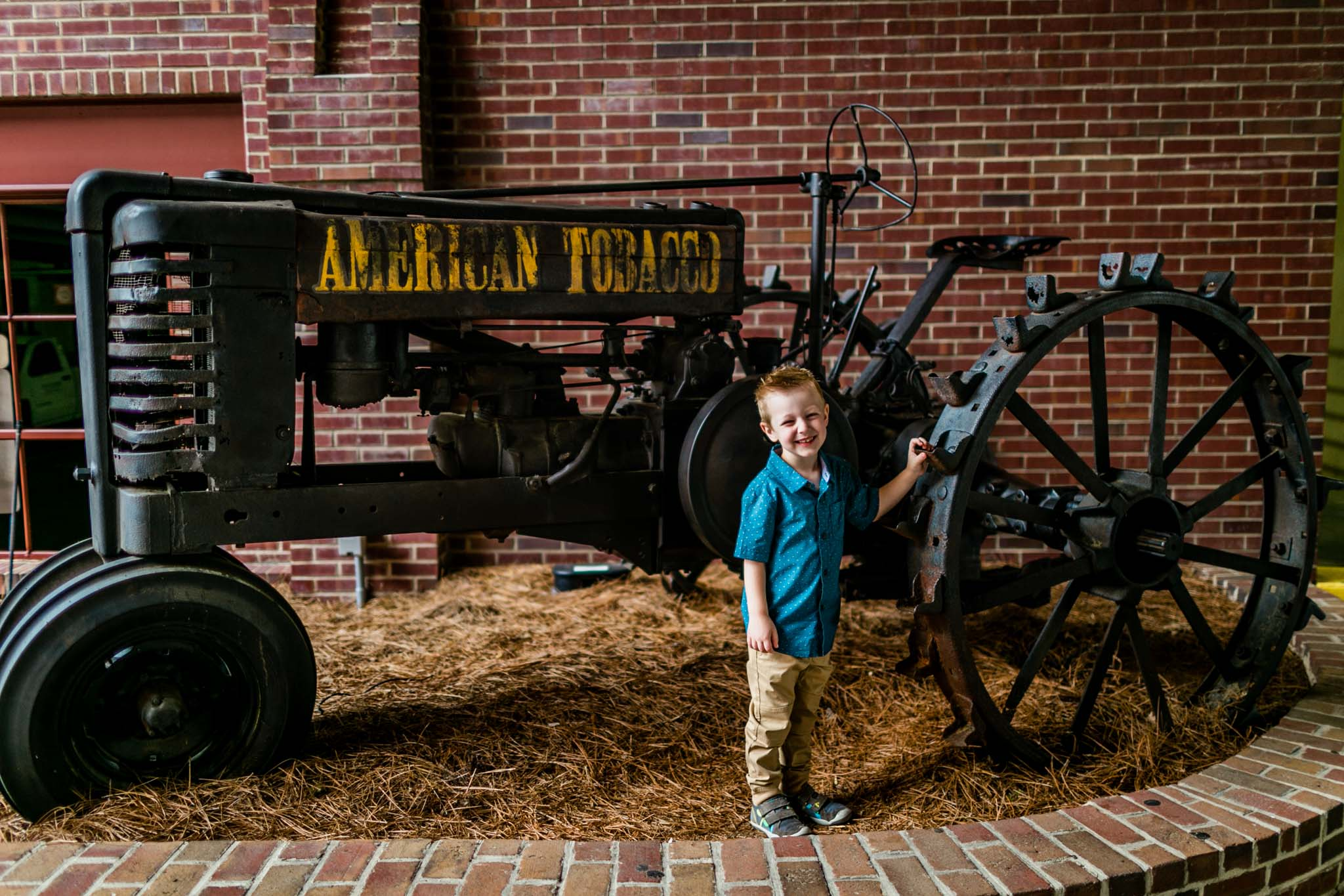 Durham Photographer | By G. Lin Photography | Young buy standing by tractor