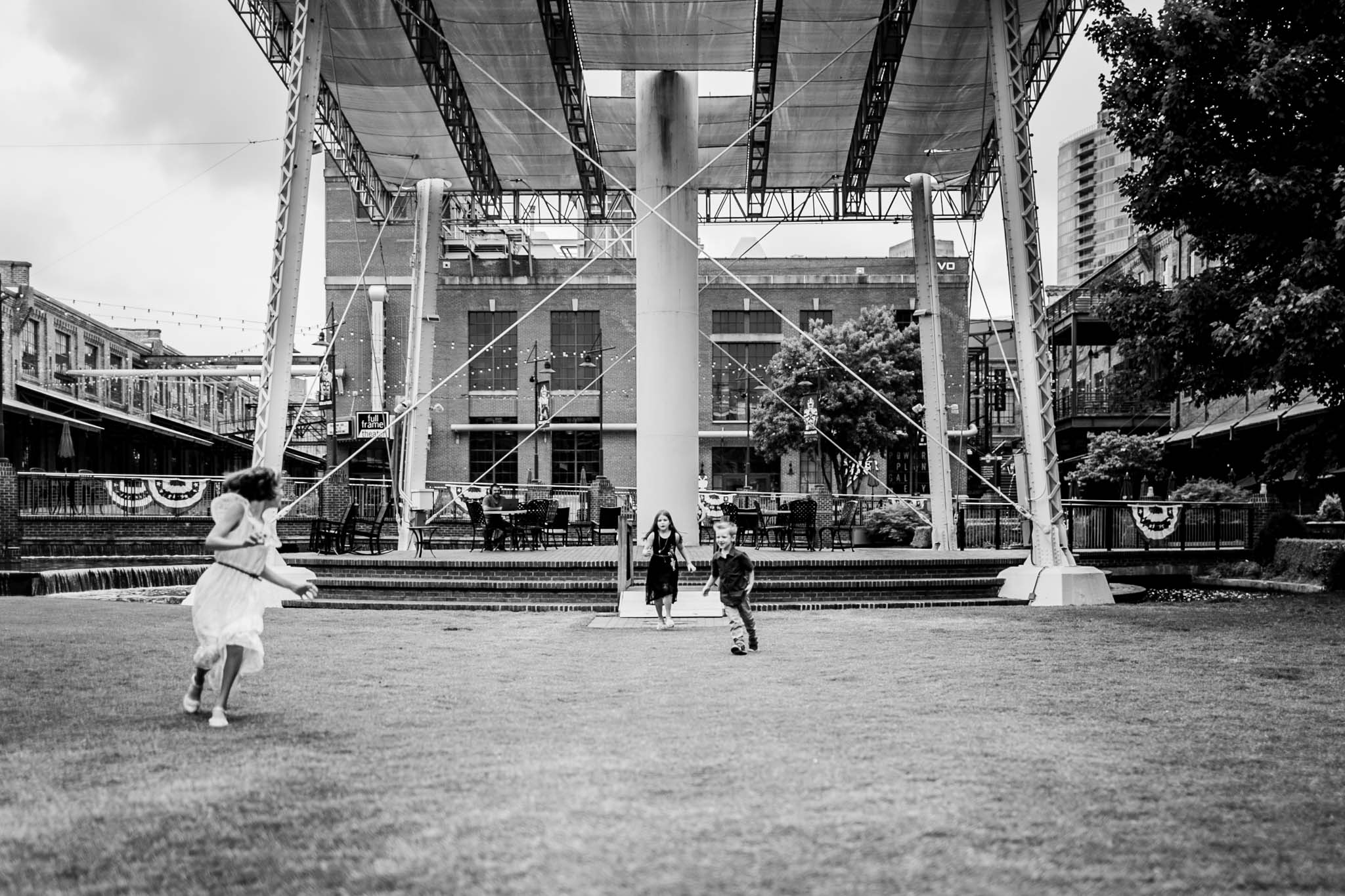 Durham Family Photographer | By G. Lin Photography | Candid black and white photo of kids running on grass at American Tobacco Campus