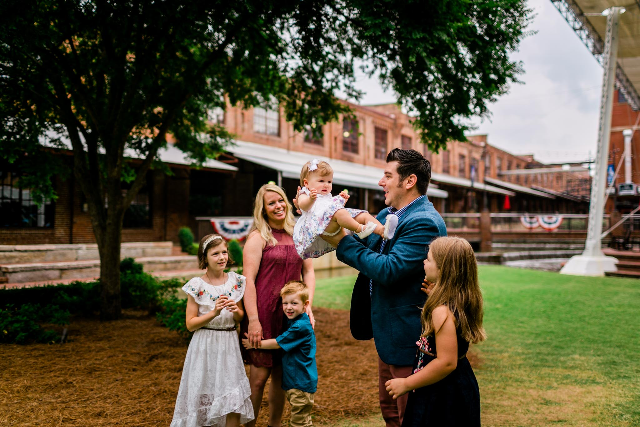 Durham Family Photographer | By G. Lin Photography | Candid lifestyle photo of dad tossing baby girl with family