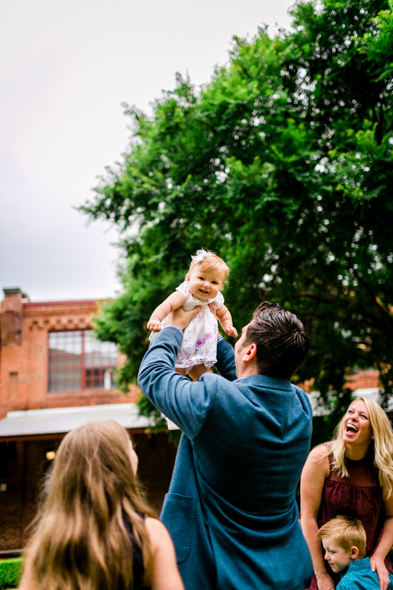 Durham Family Photographer | By G. Lin Photography | Candid lifestyle photo of dad tossing baby girl in the air