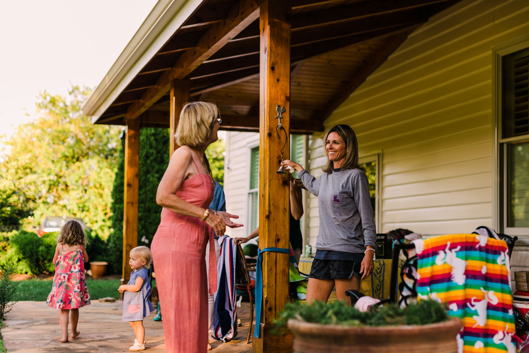 Durham Family Photographer | By G. Lin Photography | Woman ringing dinner bell outside