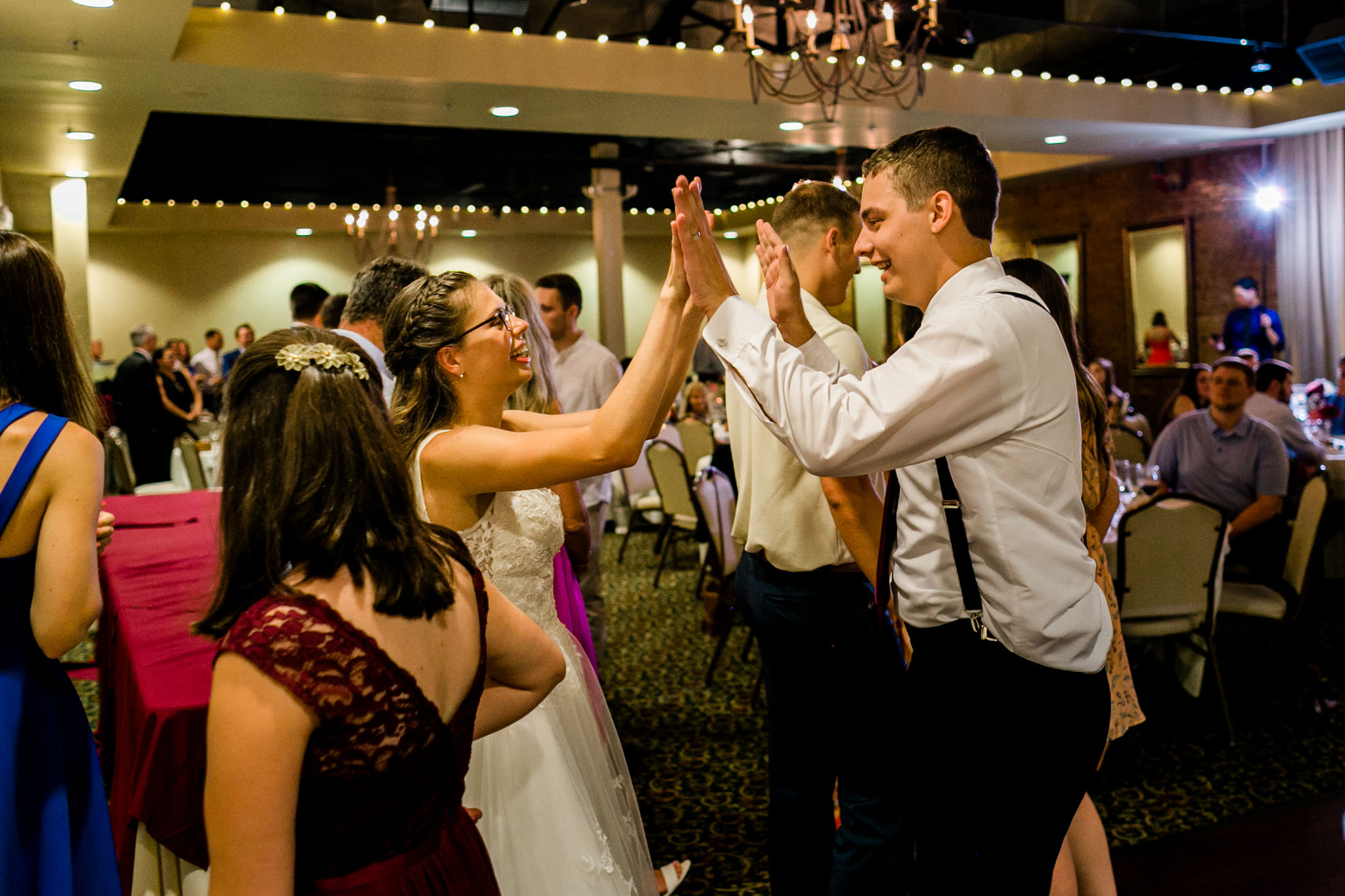 Bride and groom giving each other high fives |People dancing at wedding reception at Royal Banquet Conference Center | Raleigh Wedding Photographer | By G. Lin Photography