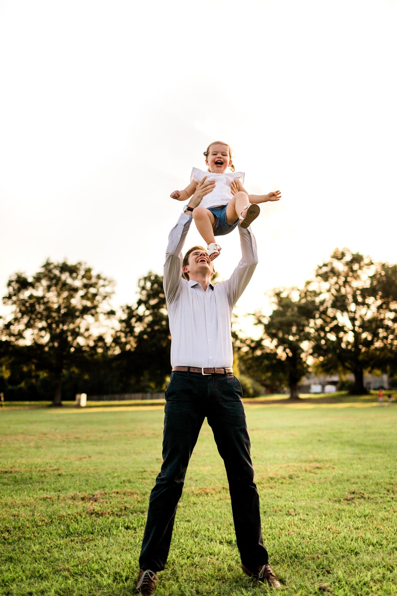 Raleigh Family Photographer at Dix Park | By G. Lin Photography | Dad throwing daughter up in the air and laughing