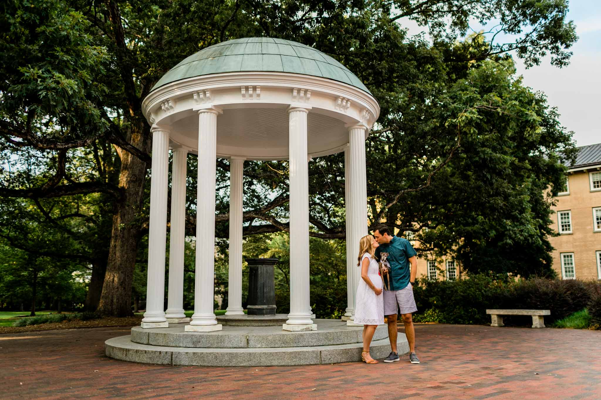 UNC Chapel Hill Maternity Photography | By G. Lin Photography | Couple kissing by the Old Well UNC