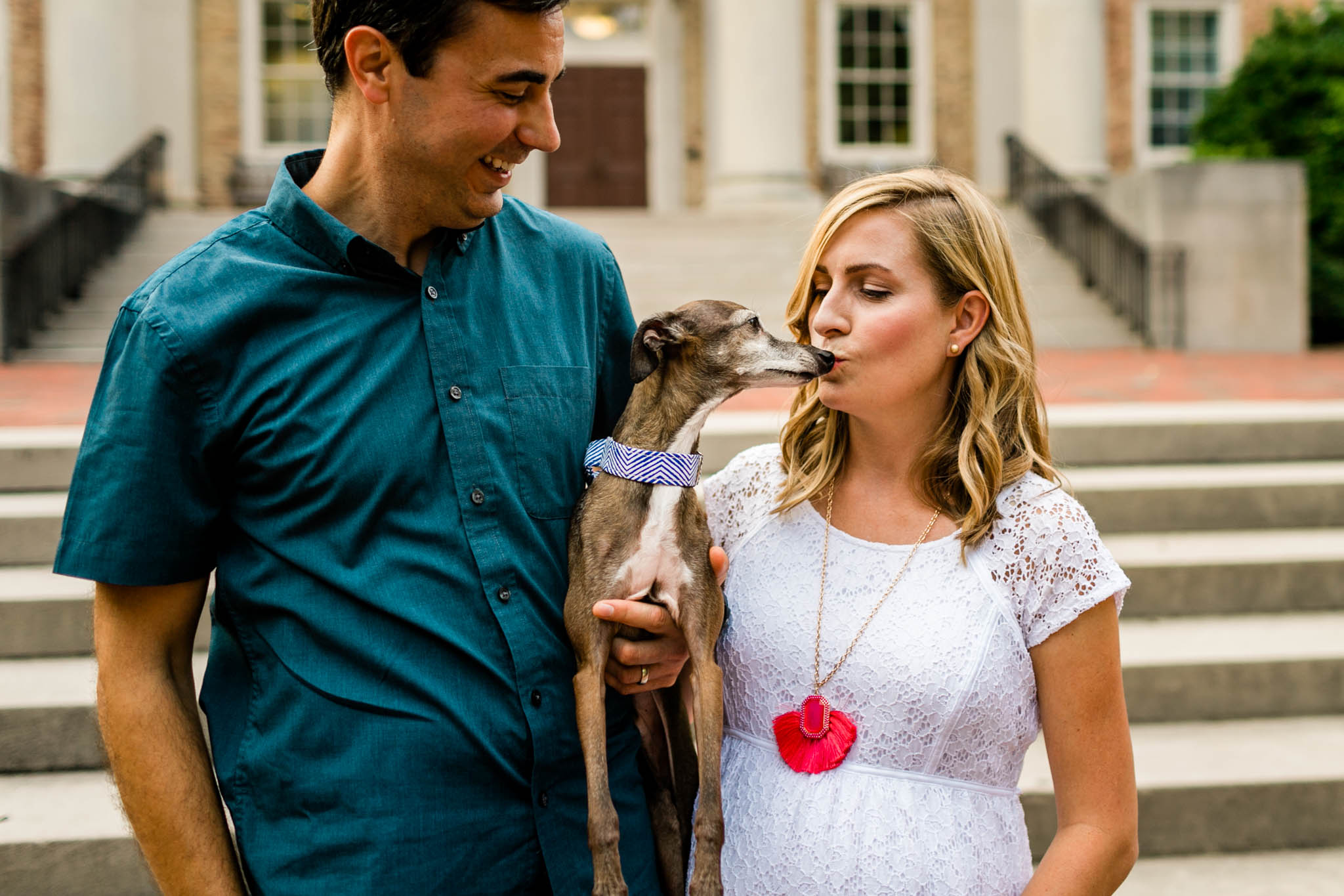 Chapel Hill Maternity Photographer at UNC | By G. Lin Photography | Couple holding dog in front of South Building and dog licking woman's face