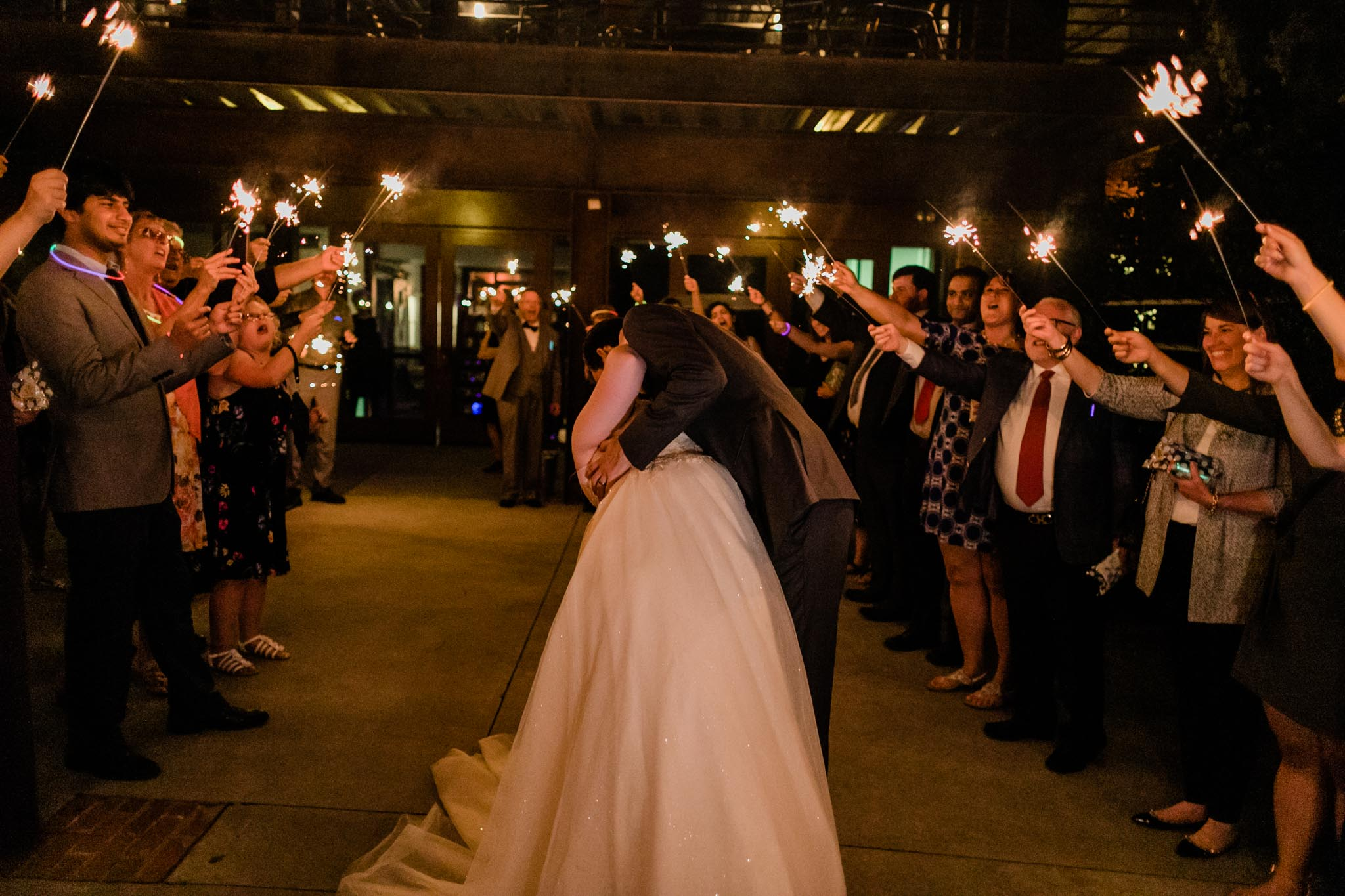 Haw River Ballroom Wedding | Durham Photographer | By G. Lin Photography | Groom kissing bride during sparkler sendoff