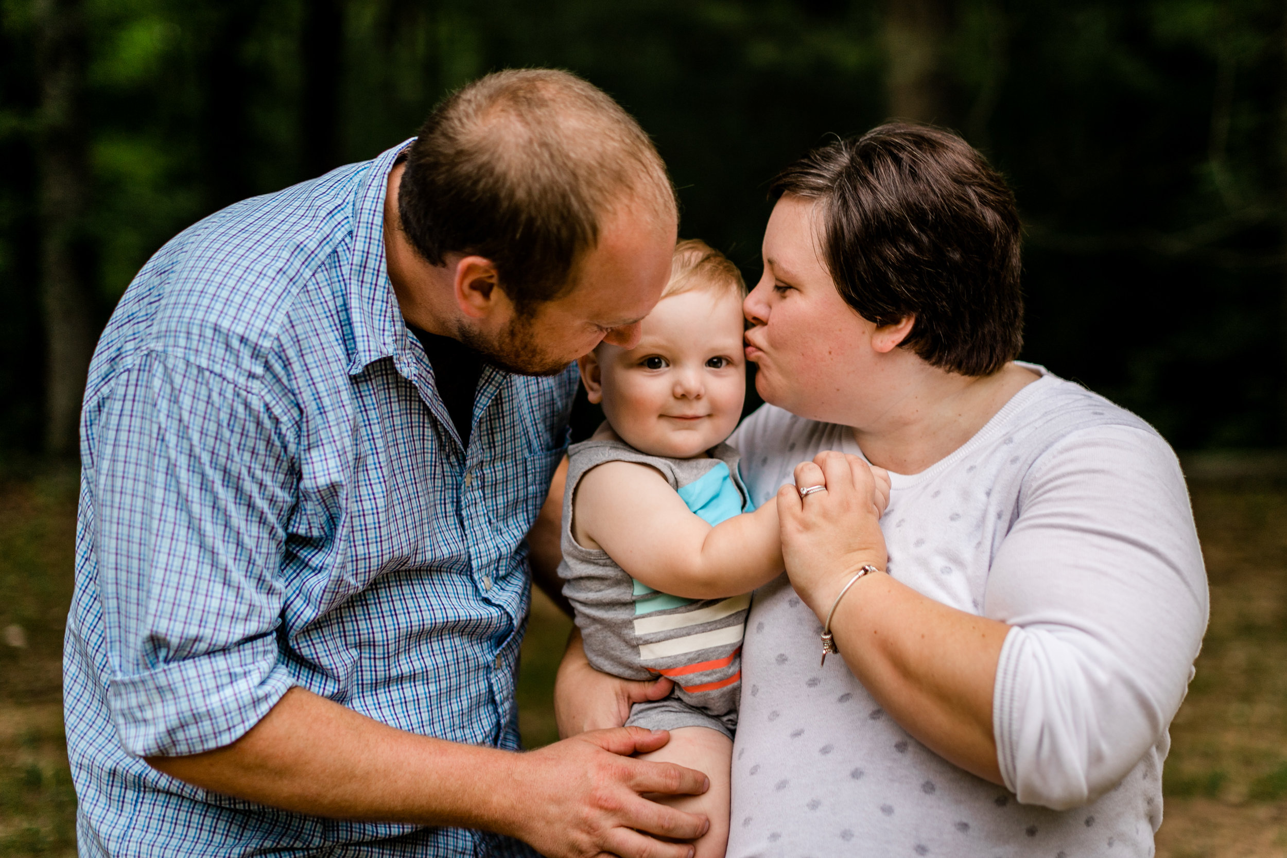 Durham Family Photographer | By G. Lin Photography | Outdoor portraits at Spruce Pine Lodge | Parents kissing son on cheeks