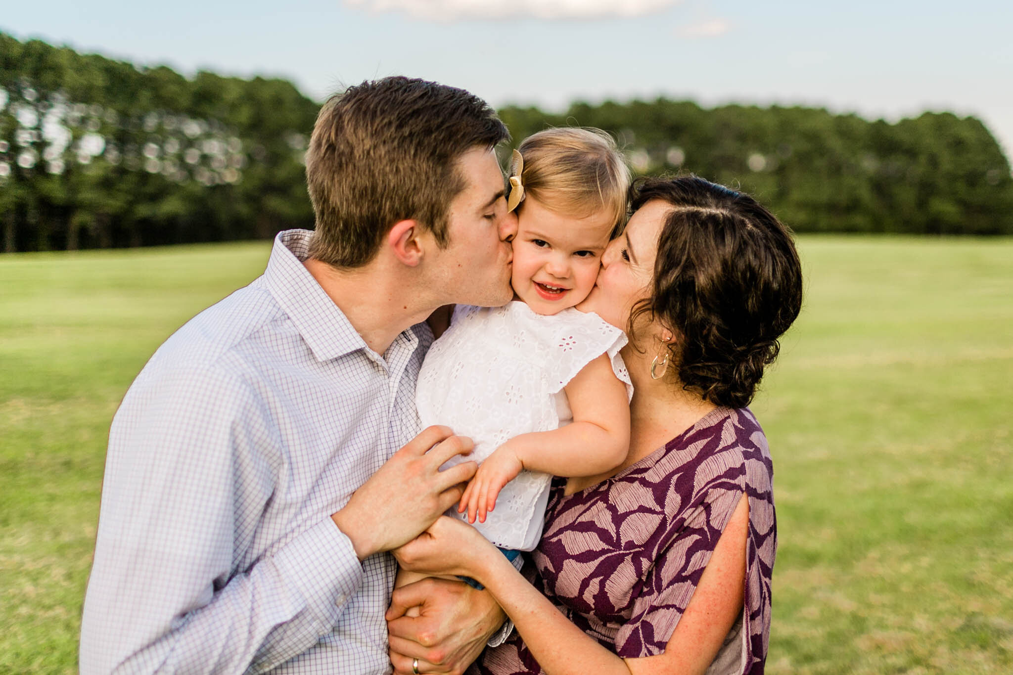 Parents kissing daughter on cheeks | Outdoor family portrait at Dix Park | Raleigh Family Photographer | By G. Lin Photogrpahy