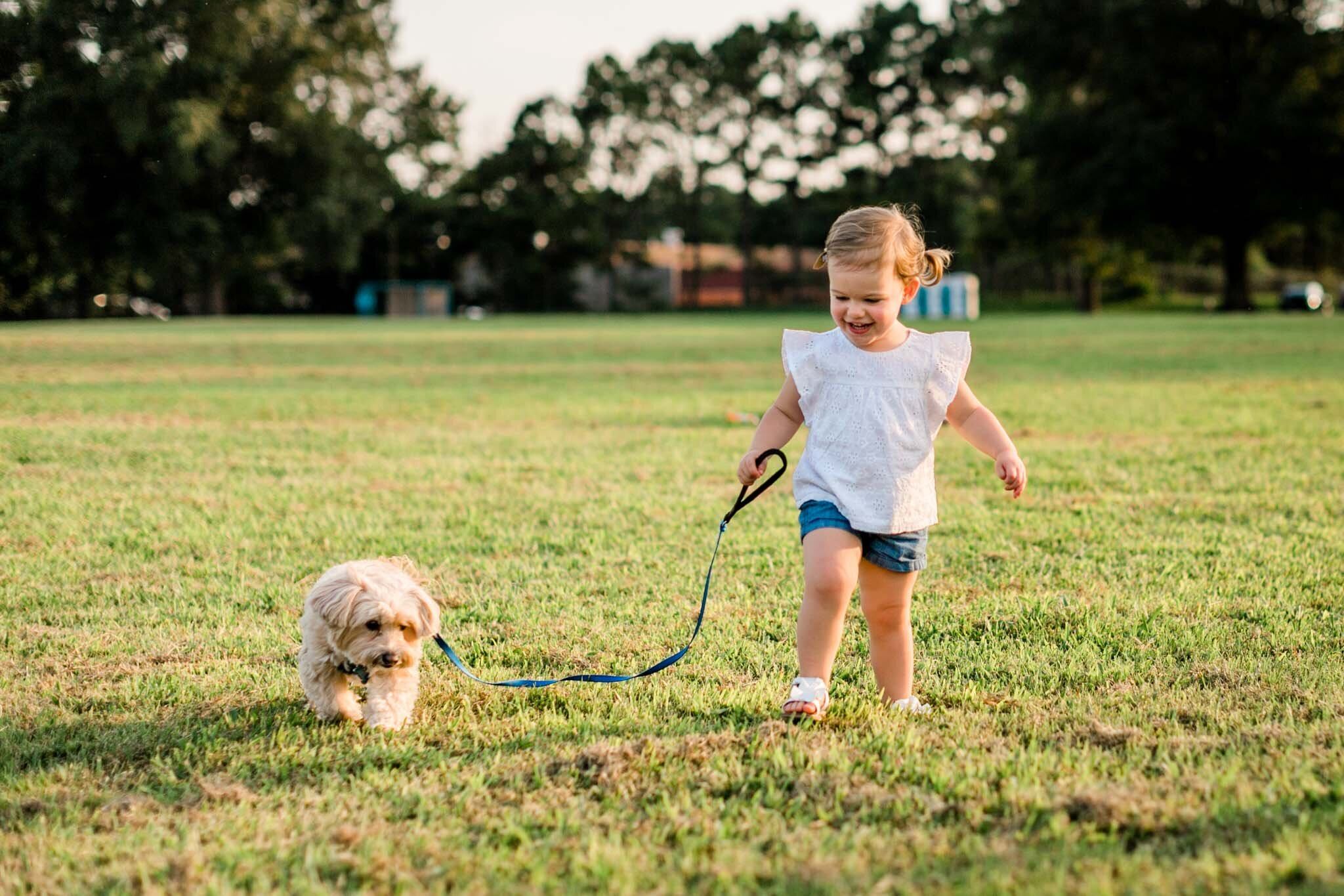 Raleigh Family Photographer | By G. Lin Photography | Little girl walking maltipoo dog