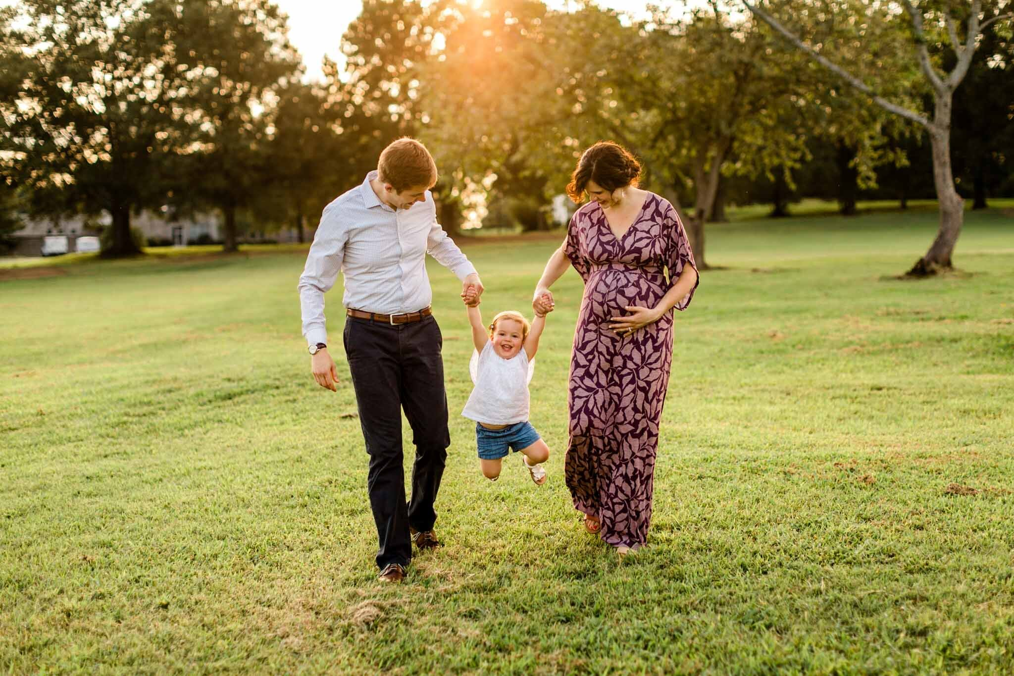 Raleigh Family Photographer at Dix Park | By G. Lin Photography | Parents swinging daughter outside