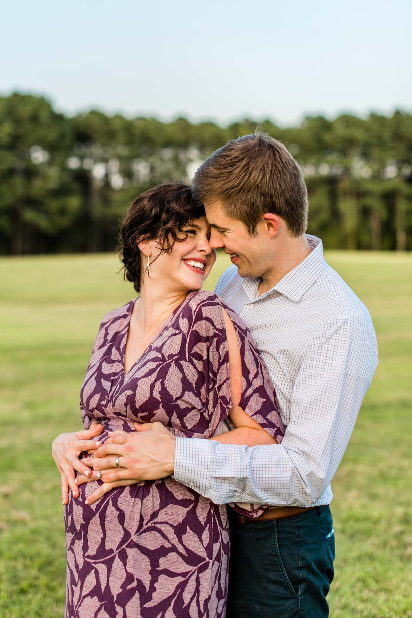 Raleigh Maternity Photography at Dix Park | By G. Lin Photography | Couple smiling together in open field