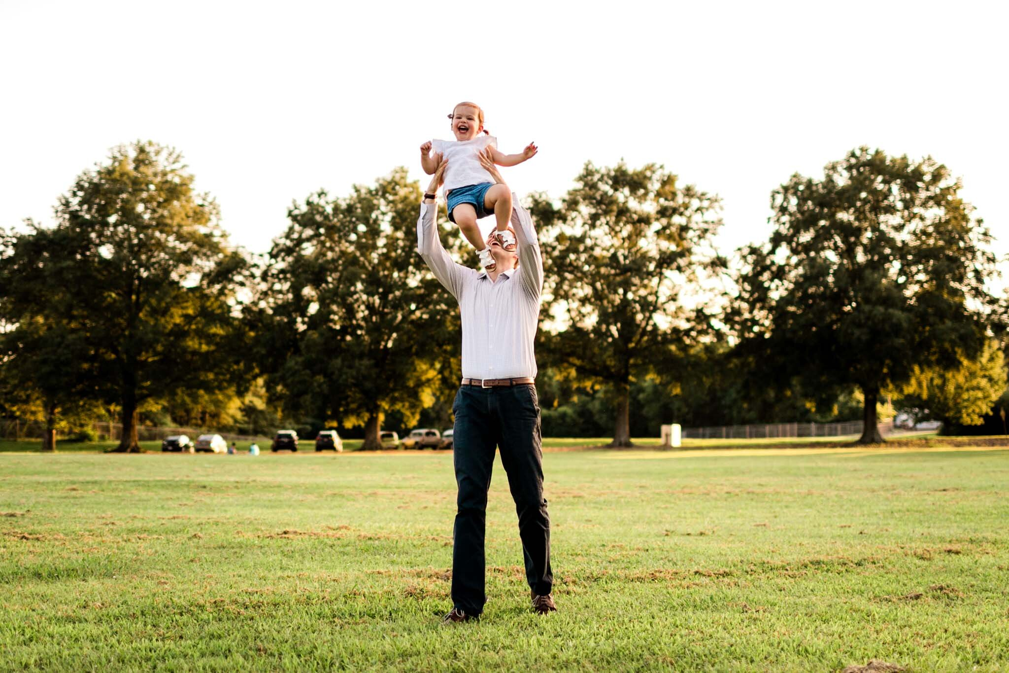 Raleigh Family Photographer at Dix Park | By G. Lin Photography | Dad tossing daughter in air at open field