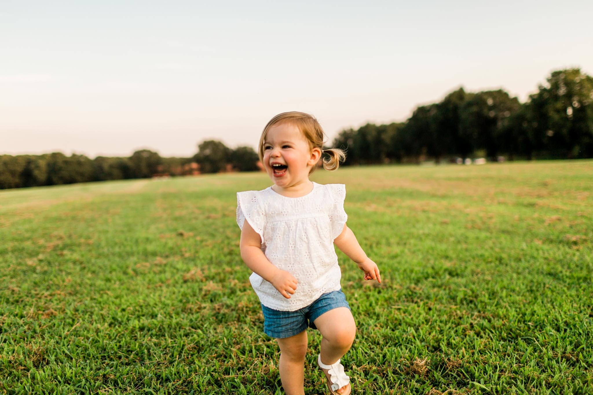 Girl running in open field during sunset at Dix Park | Raleigh Family Photographer | By G. Lin Photography