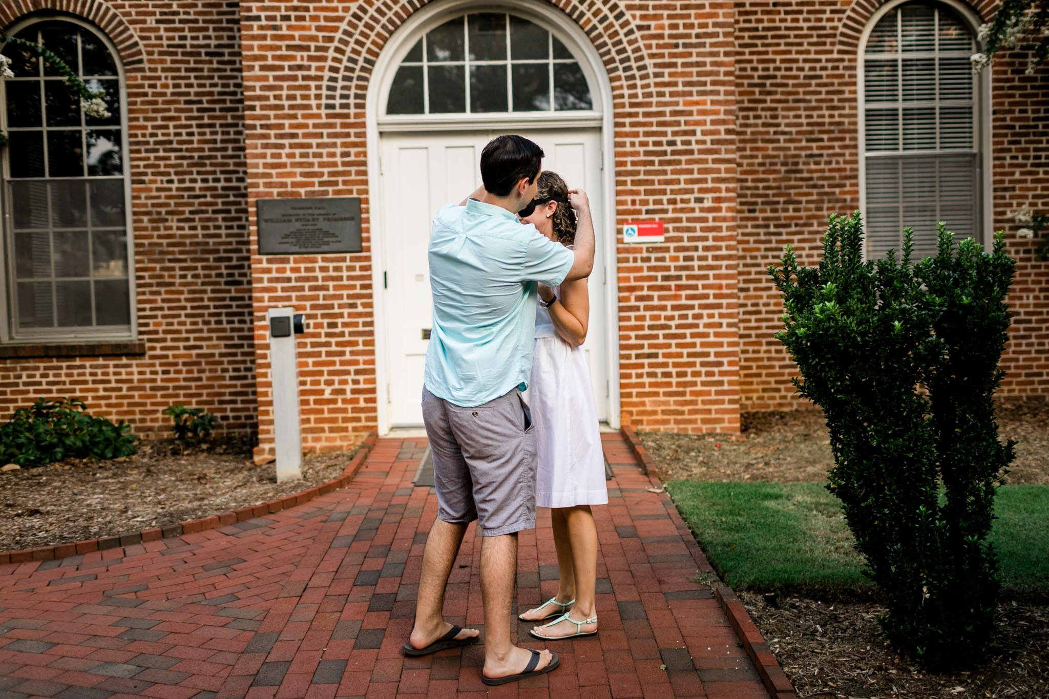 Engagement Photography at NC State | Primrose Hall | By G. Lin Photography | Raleigh Proposal Photographer | Man taking off blindfold from woman
