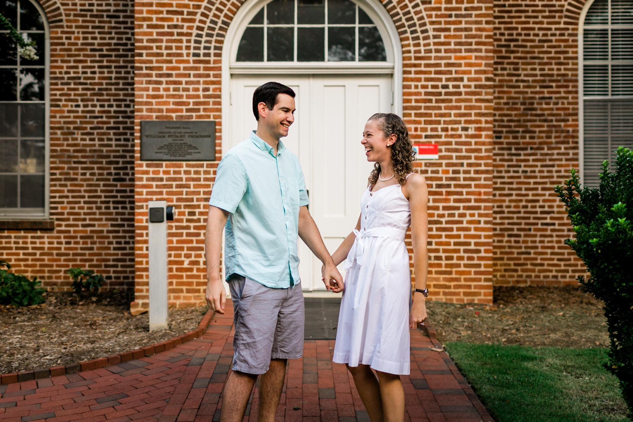 Raleigh Engagement Photographer | NC State University | By G. Lin Photography | Couple laughing together in front of building