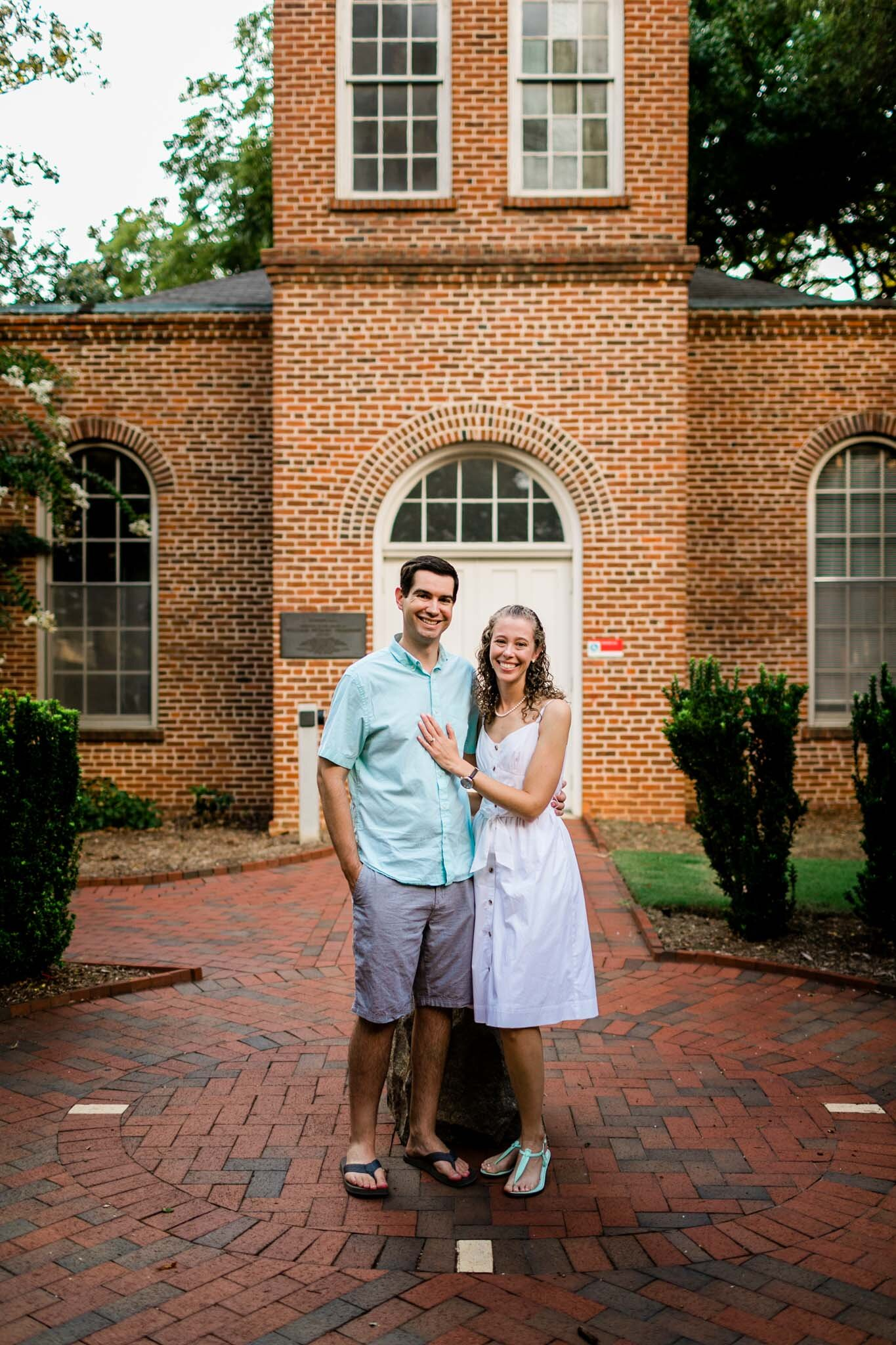 Raleigh Engagement Photographer | NC State | By G. Lin Photography | Couple taking photo in front of Primrose Hall