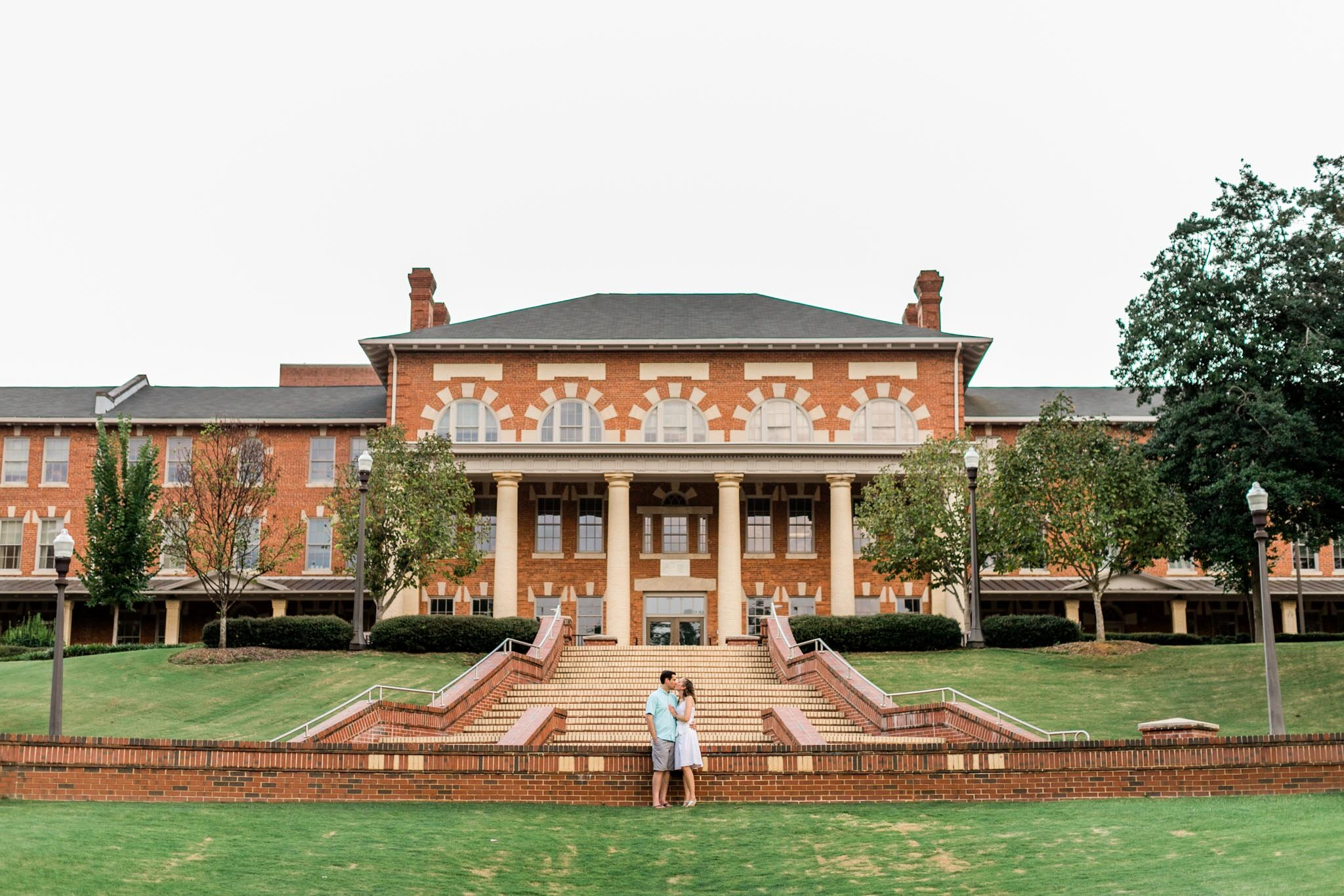 Raleigh Engagement Photographer | NC State University | By G. Lin Photography | Wide shot of couple standing in front of building