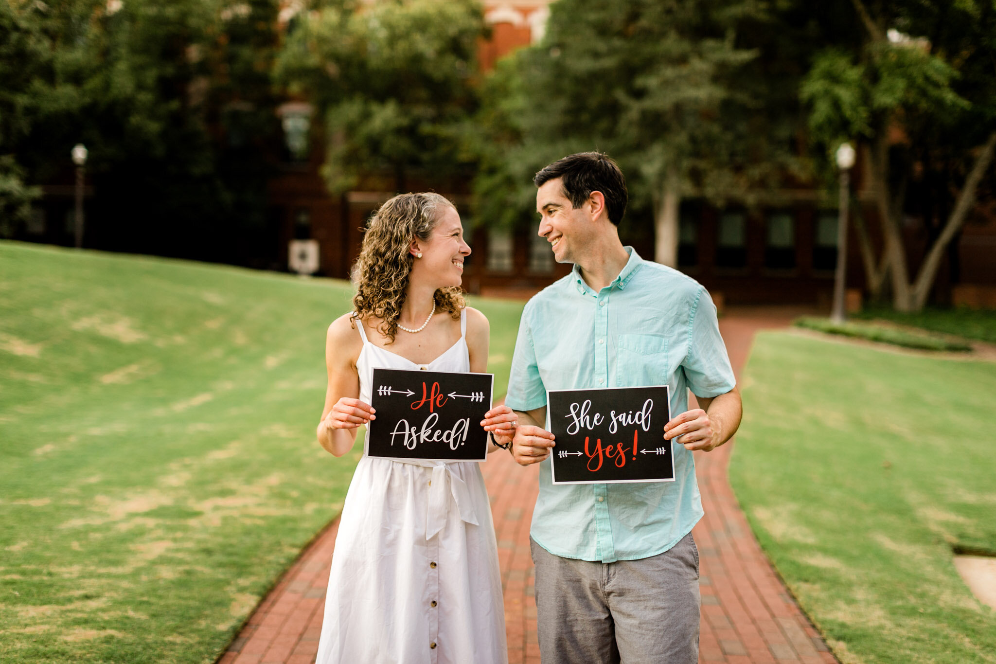 Raleigh Engagement Photographer | NC State University | By G. Lin Photography | Couple holding signs of engagement