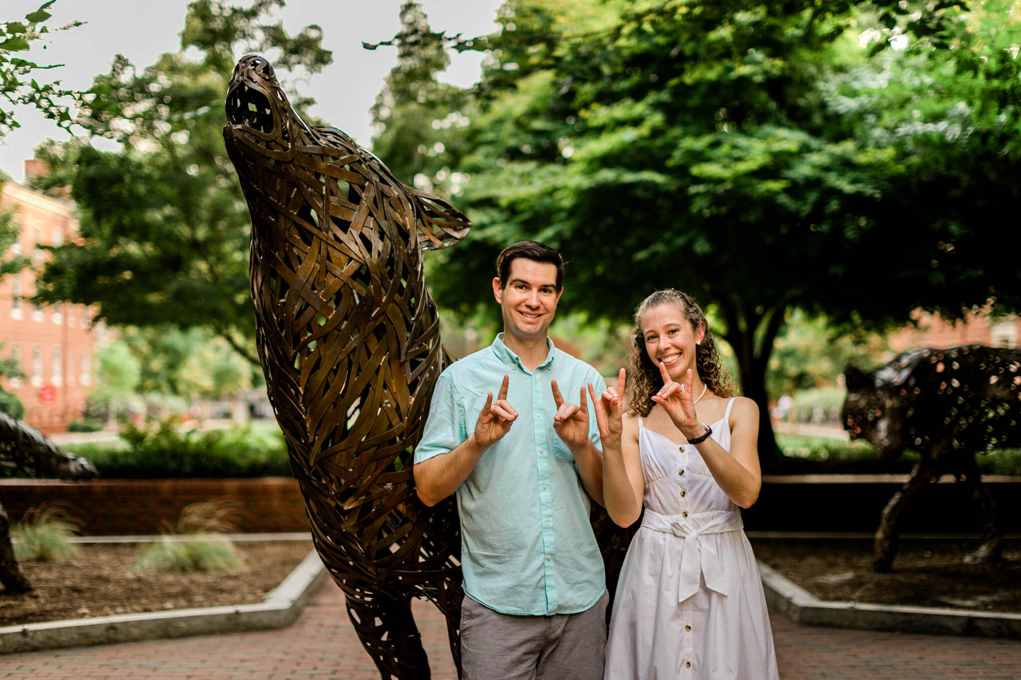 Raleigh Engagement Photographer | NC State University | By G. Lin Photography |  Couple making wolfpack signs and standing next to wolf statue