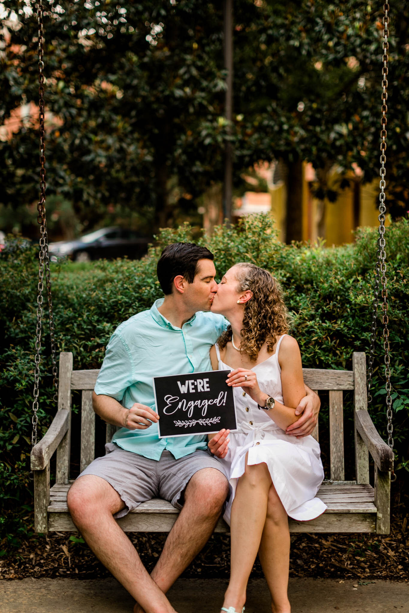 Raleigh Engagement Photographer | NC State University | By G. Lin Photography | Couple sitting on bench and holding engagement sign