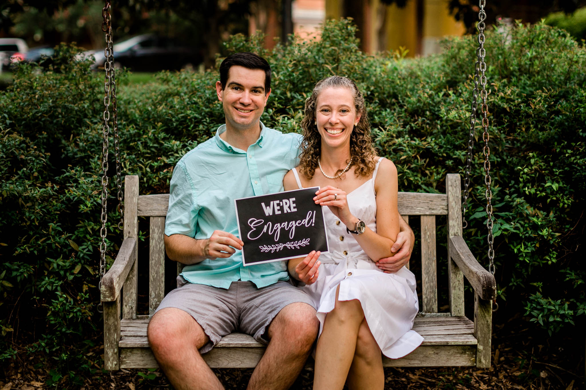 "Raleigh Engagement Photographer | NC State University | By G. Lin Photography | Couple holding ""we're engaged"" sign and sitting on bench"
