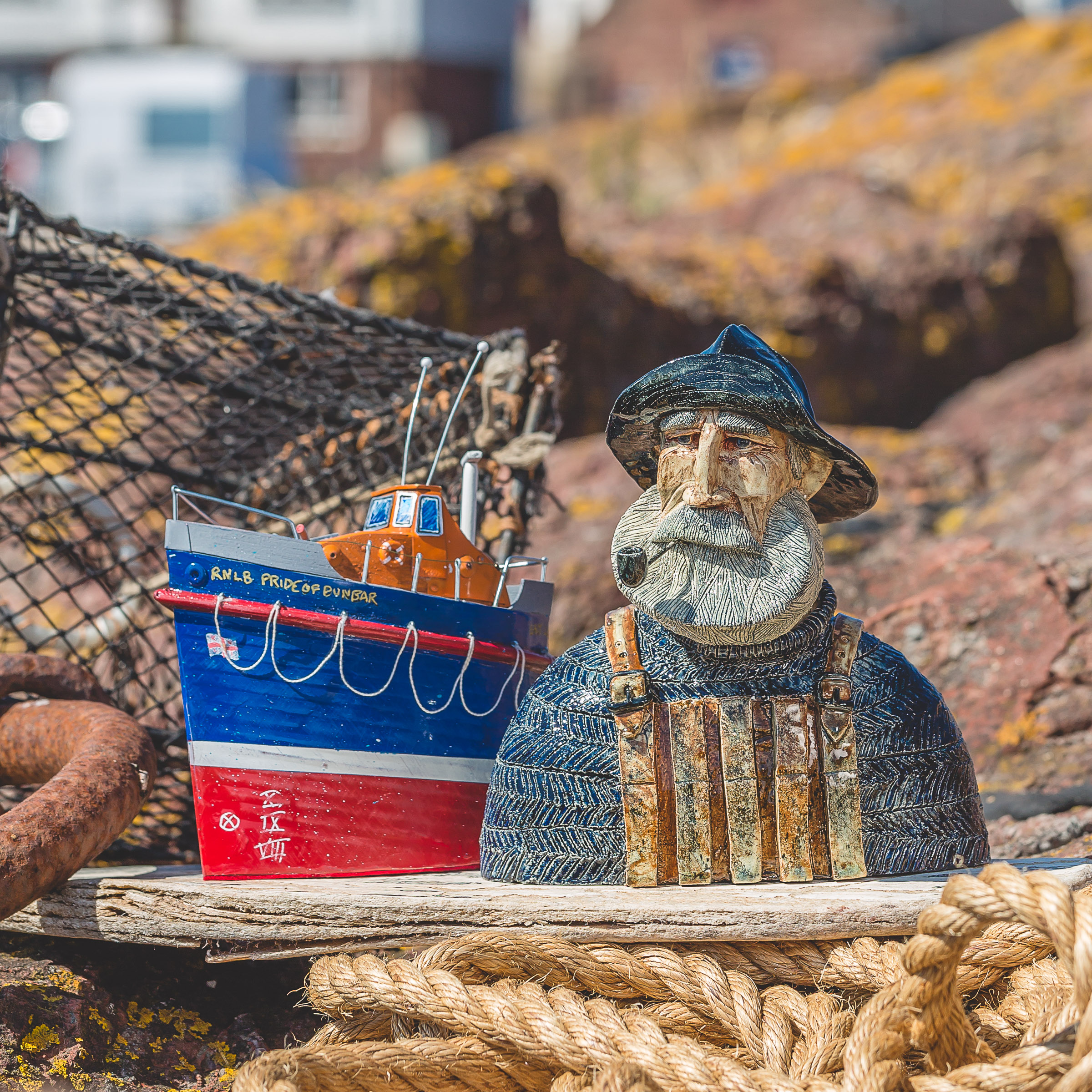 The two pieces auctioned – the rugged lifeboat man designed by Suffolk-based Joe Lawrence and the lifeboat created from recycled objects by Seth Draper (photo by Nick Mailer)