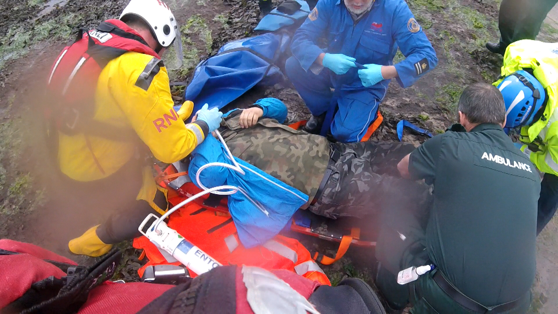 Crewman Jamie Forrester reassures the casualty while paramedics strap the broken leg.
