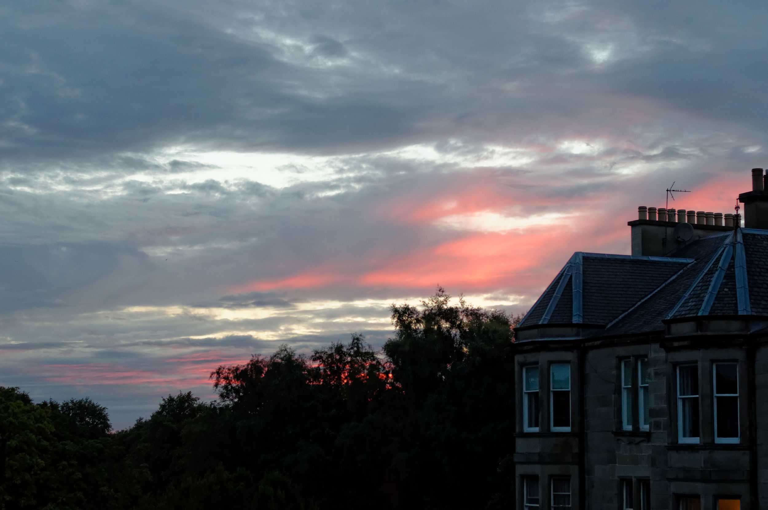 An August sunset viewed from our living room window. The buildings are of a similar style to ours.
