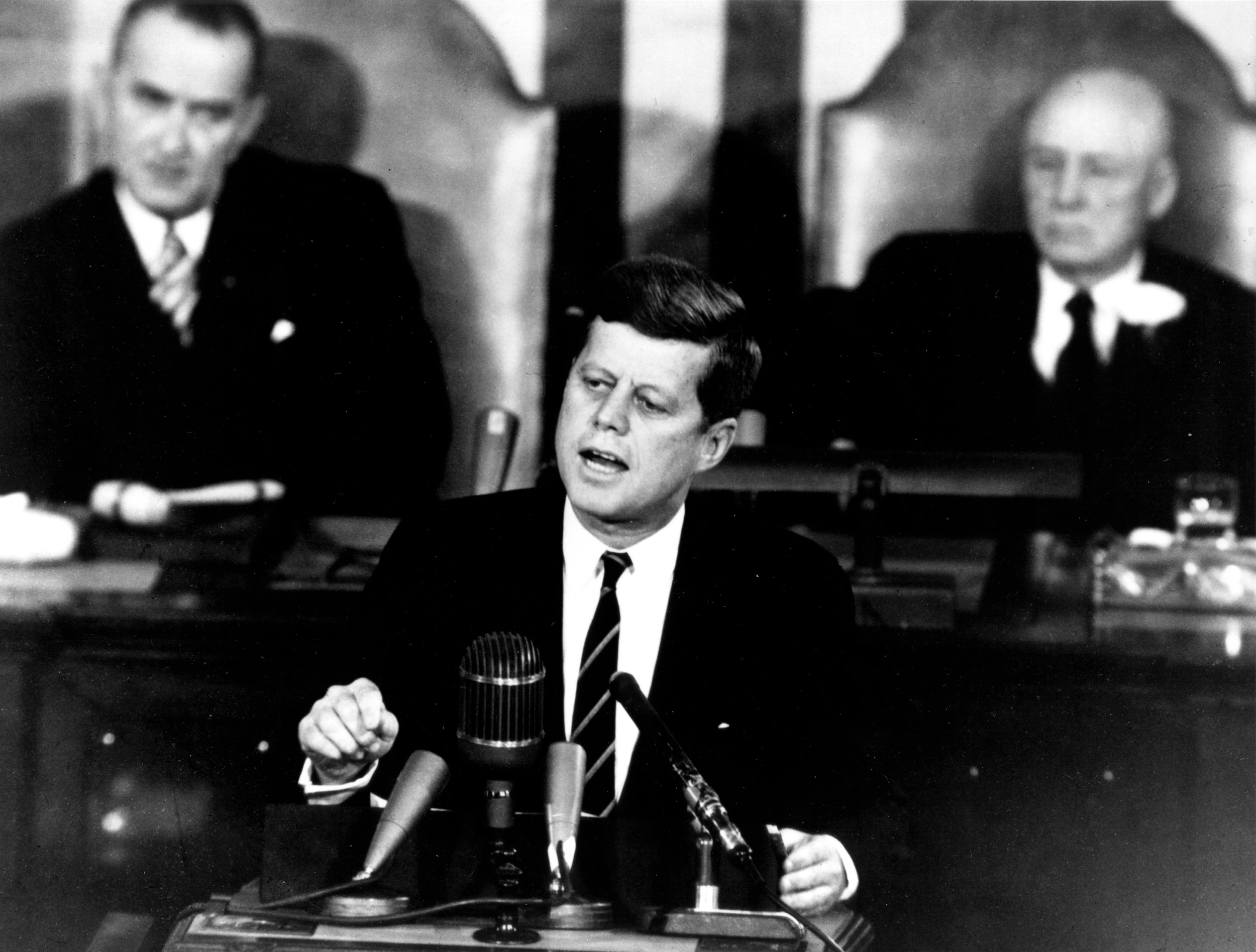 President Kennedy Addresses Congress May 25, 1961. Shown in the background are, (left) Vice President Lyndon Johnson, and (right) Speaker of the House Sam T. Rayburn. Image #:  70-H-1075 .