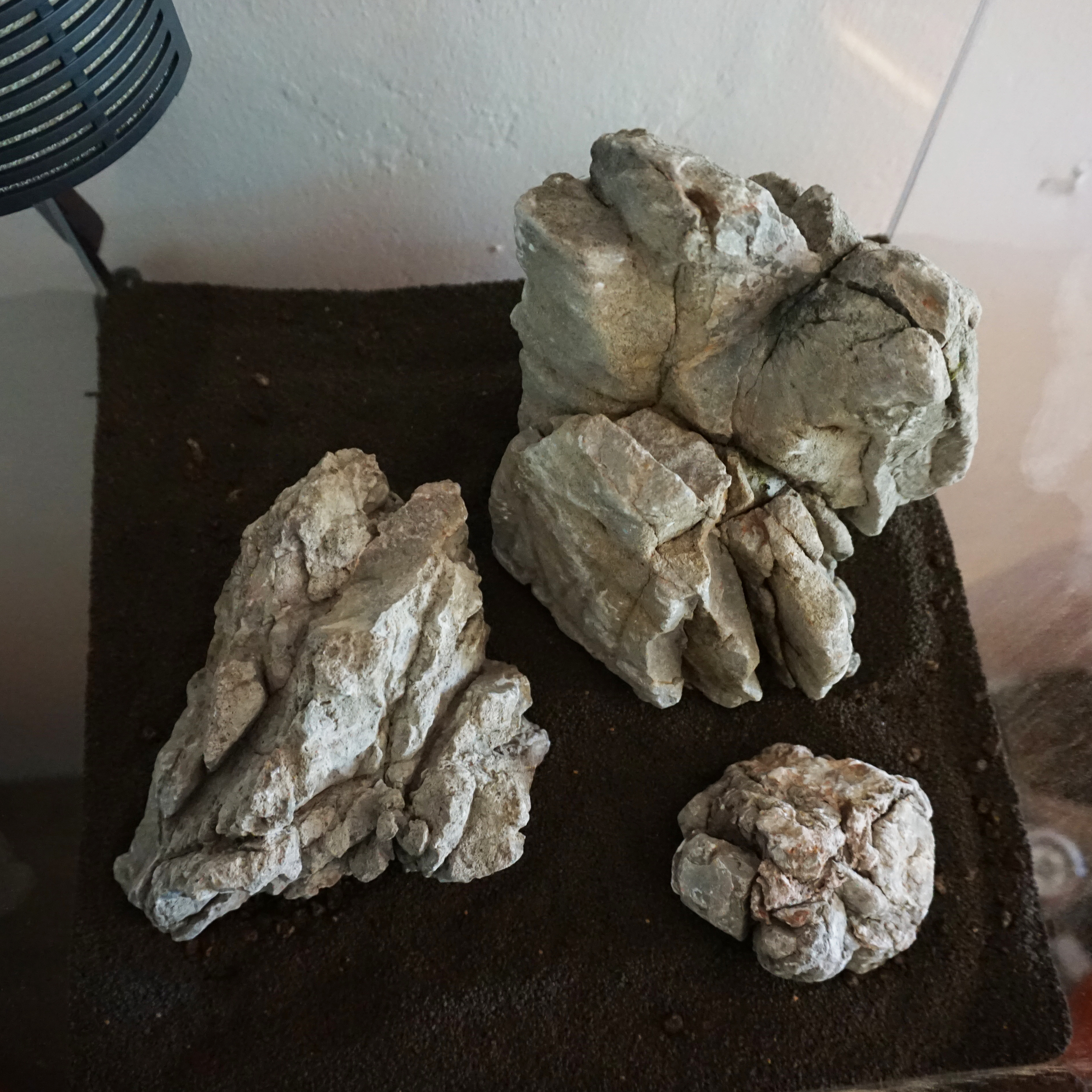 """Once your design is finalized, you can now take more substrate and add it to the tank. You may want to bring the substrate up higher in one area over another or partially bury asection of rock or wood. In other words, create a three dimensional space. When you are done, you will want about 2.5"""" to 3"""" of coverage throughout. Some areas can have slightly more, and some less depending on the overall design. Do not rush through this part of the set-up. Taking the night to sleep on it will go a long way later when you wish you would have done things differently. It is much easier to make slight changes without water in your aquarium."""