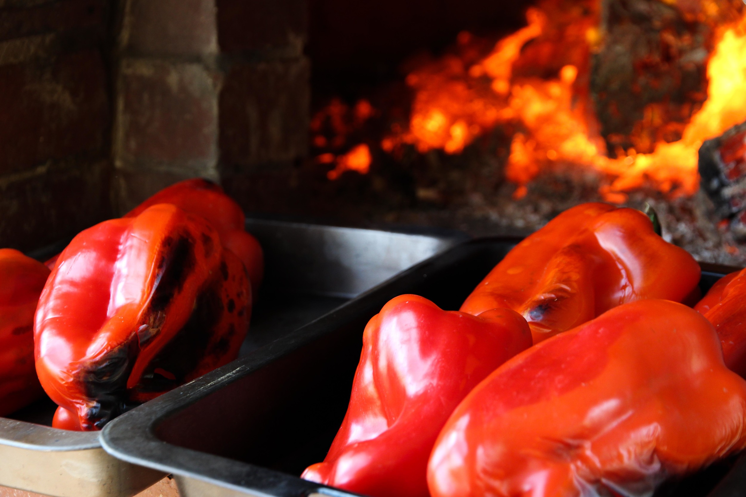 Capsicum chargrilling in front of the wood fire oven