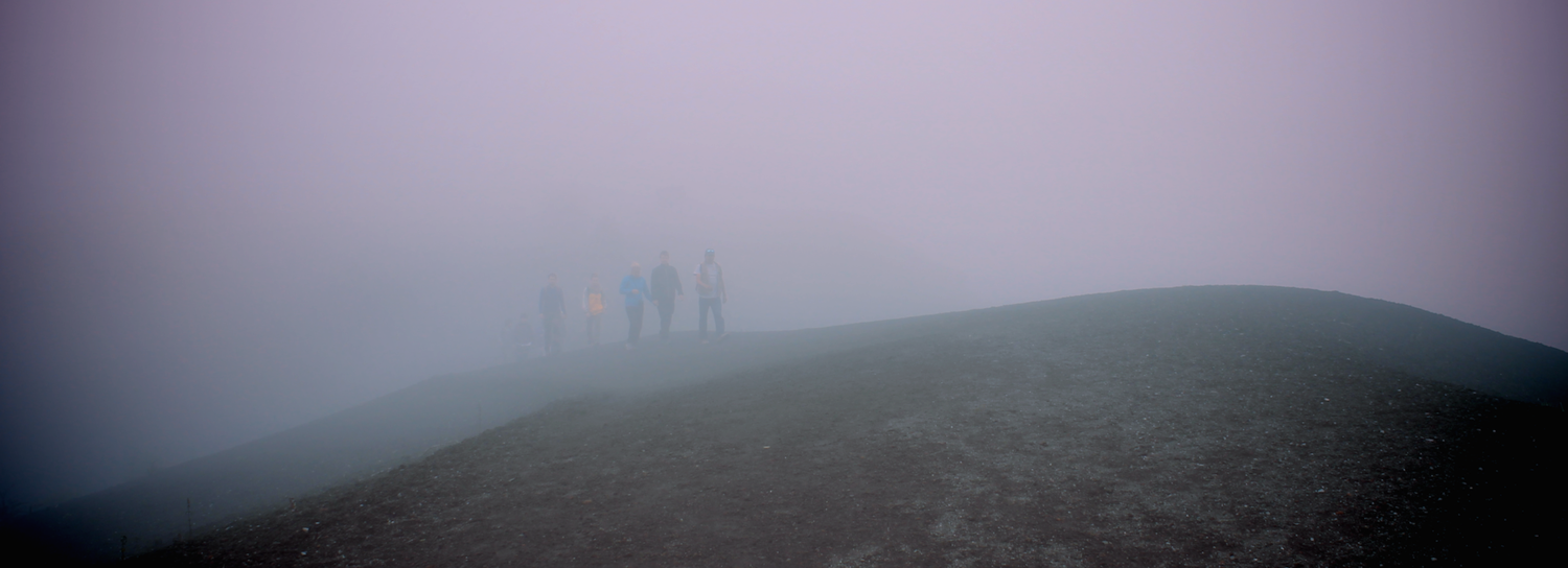A tour group emerging from the mist on top of Volcan Pacaya, near Antigua.
