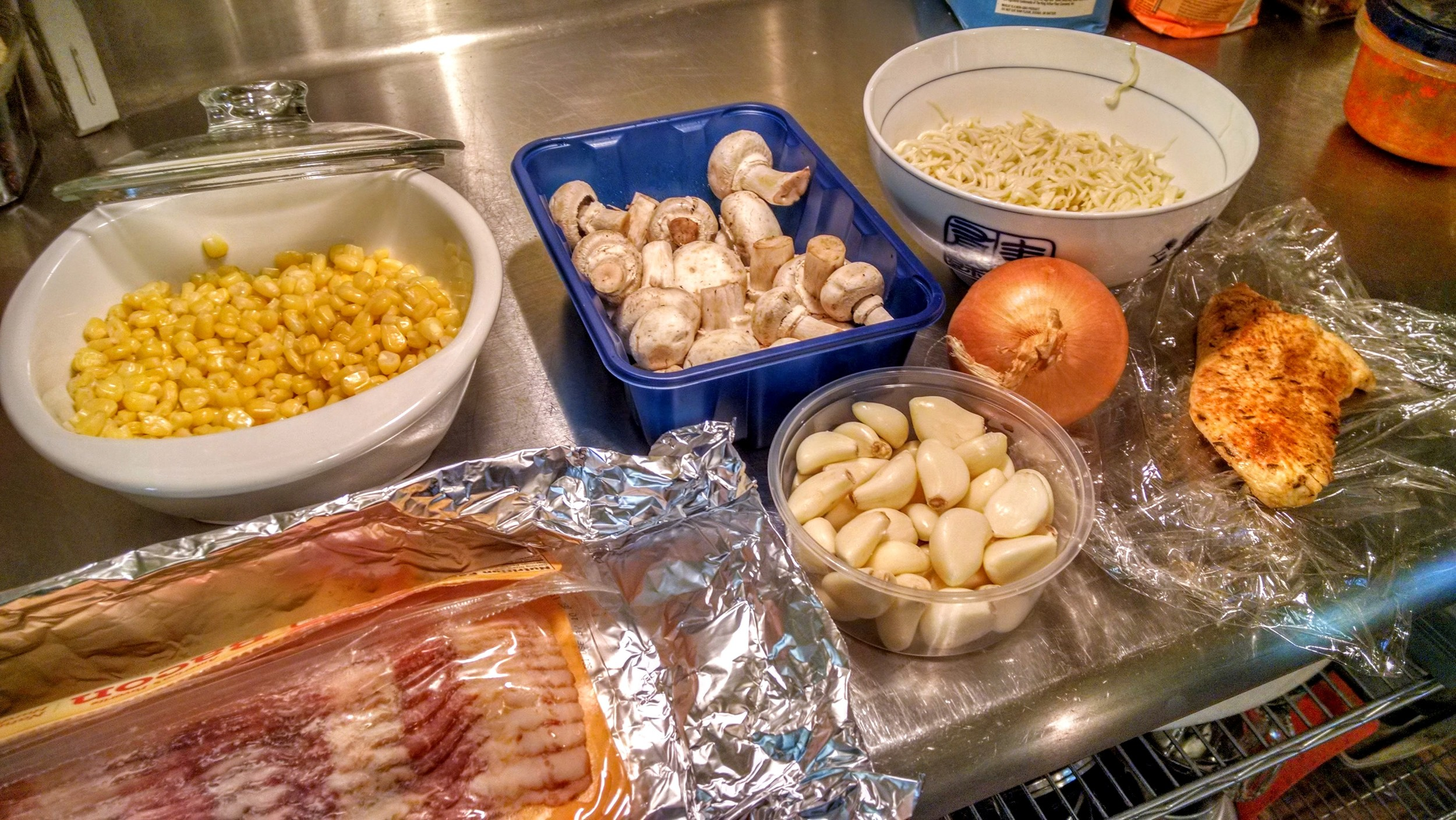 Sweet Corn (from frozen), button mushrooms, homemade pasta, bacon, garlic, onions and roasted chicken breast. Cheddar cheese will be added on top at the end.