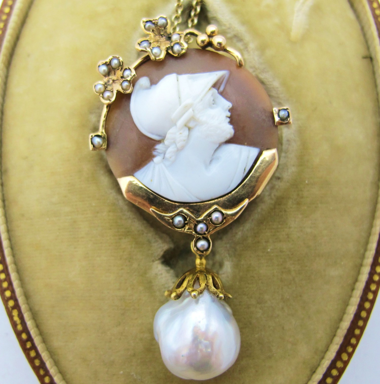 Victorian shell cameo featuring profile of Greek soldier. Framed in 14k yellow gold and seed pearls, with baroque pearl dangle. Can be worn as brooch or pendant.
