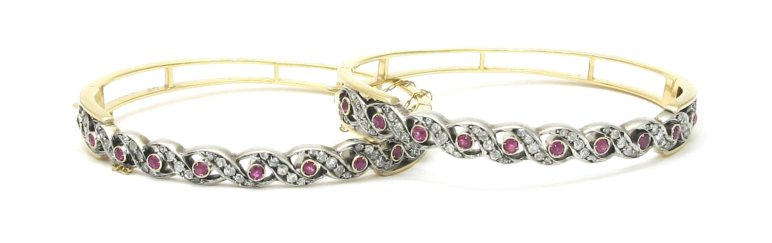 Pair of small graduated diamond and ruby bangles set in silver on 14K gold. Each bangle has 49 diamonds and 10 rubies for a total approximate diamond carat weight of 2.14 and a total approximate ruby carat weight of 2.40.