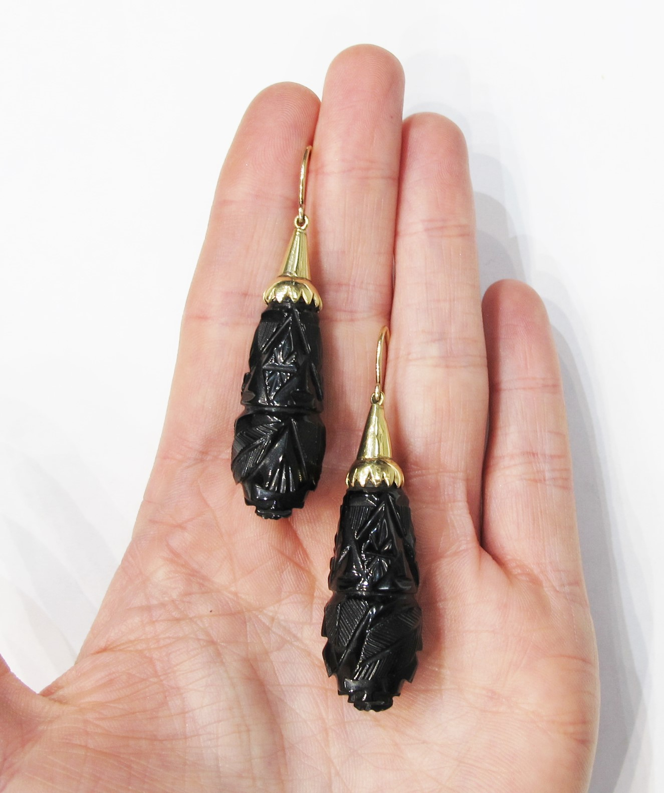 Extra-long Victorian drop earrings of carved jet with saw-tooth gold caps.