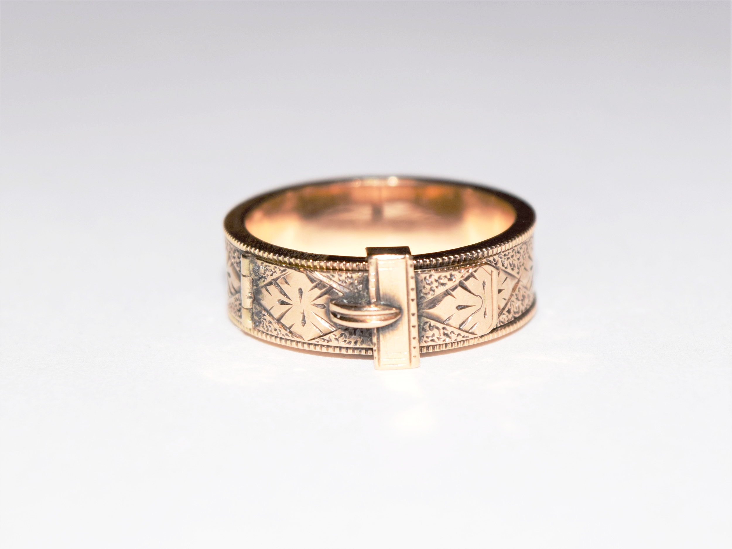 A 15K rosy gold locket ring with a buckle design and hand engraving, made c.1830.