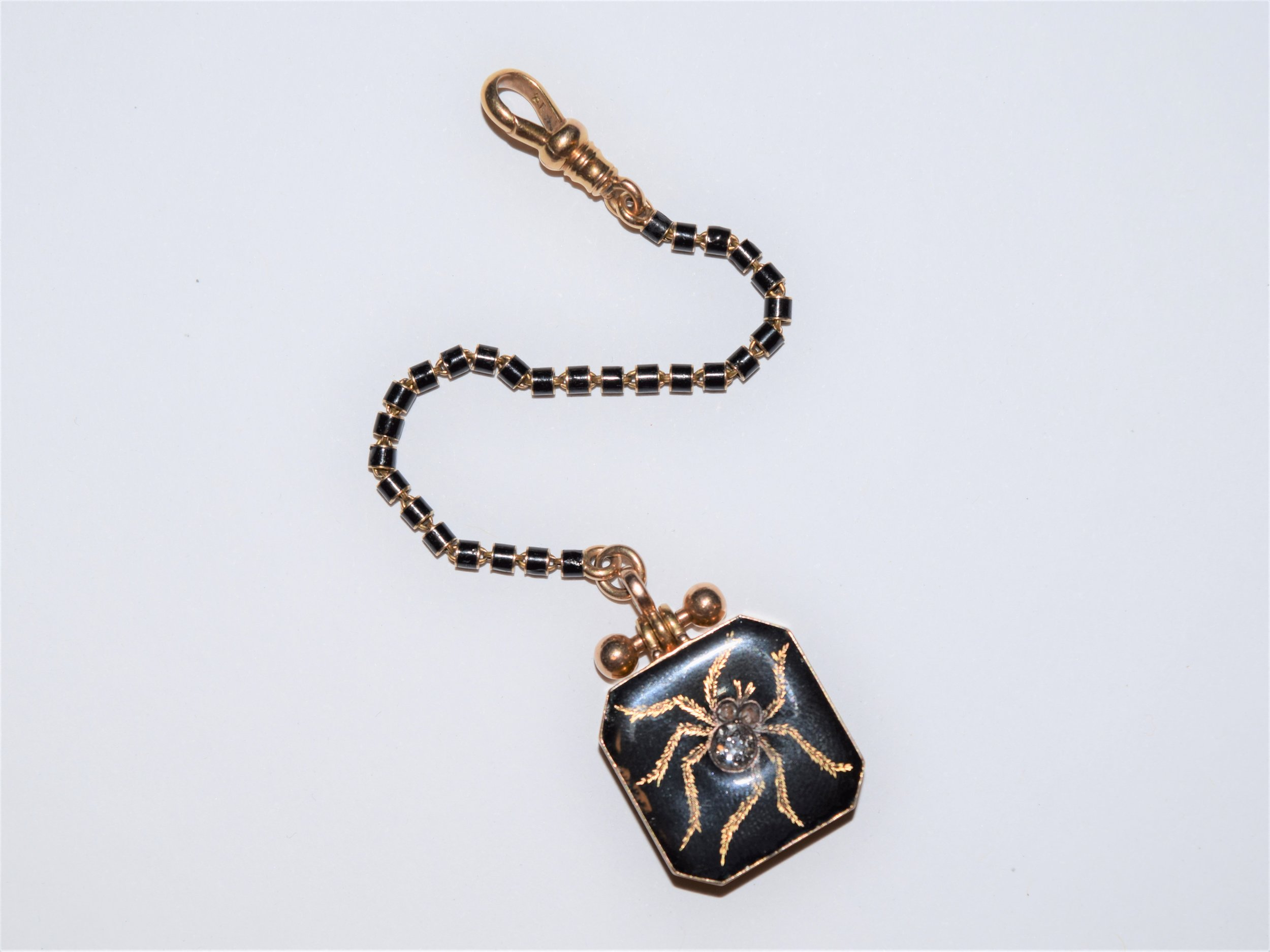 Early 20th Century 14K gold locket watch fob with black enamel and a spider design set with an old mine cut diamond.