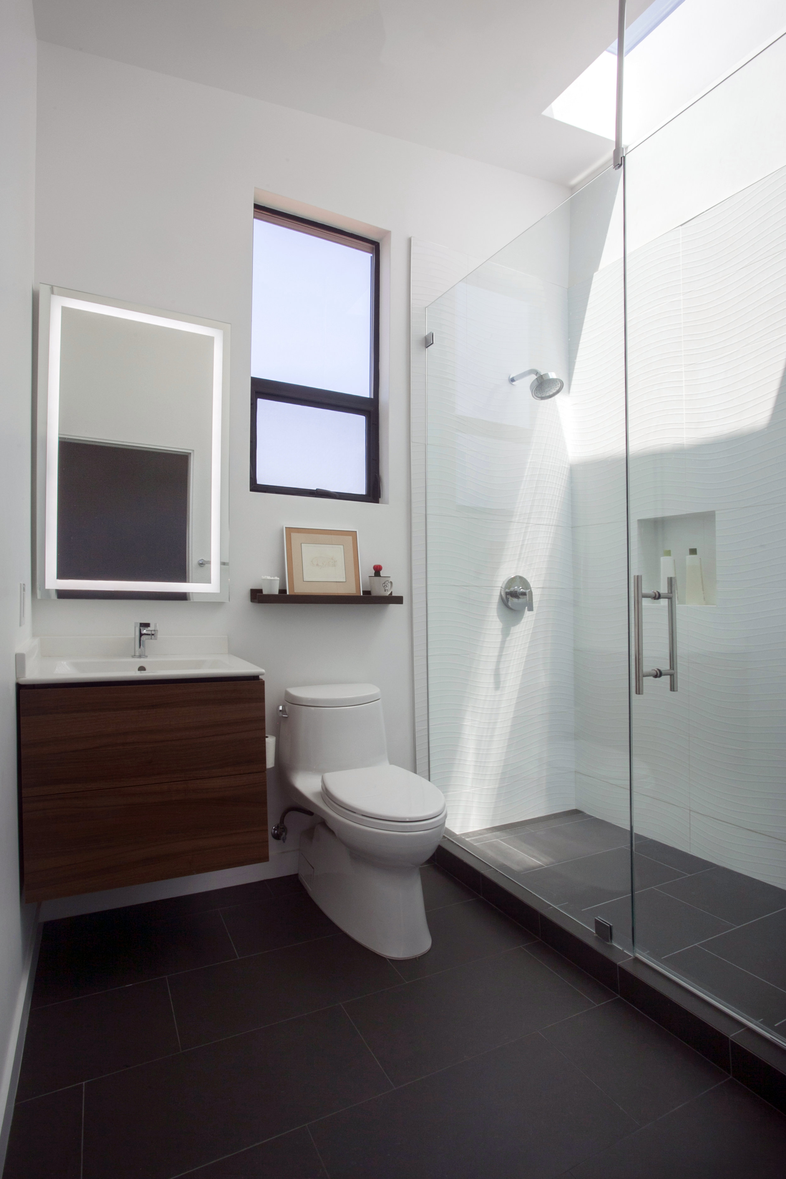The ensuite bathroom for the second upstairs bedroom picks up on details from the master bathroom - walnut cabinets, 3D tile washed by light, and dark tile floors.