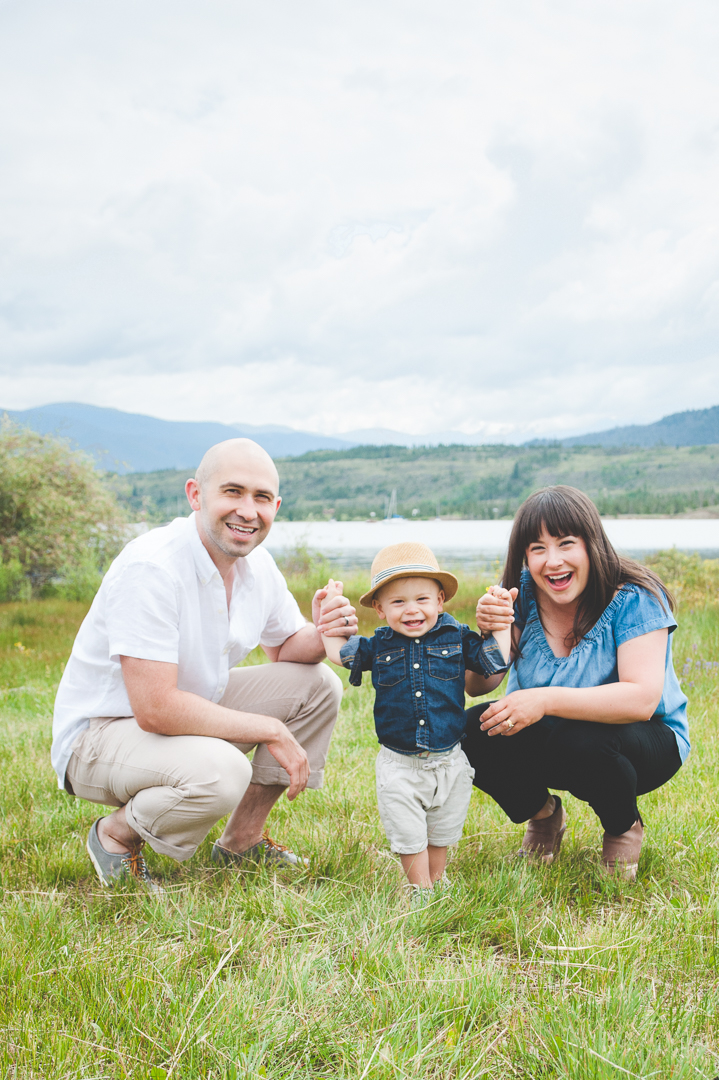 Mom and Dad get on their son's level and help him stand for a happy photo at their Lake Dillon family photo session, in the heart of the Colorado Rocky Mountains.