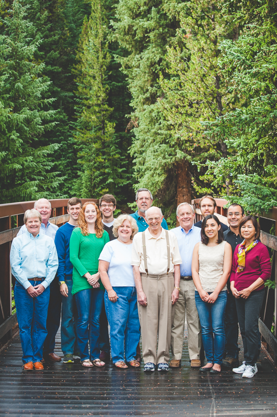 a large family group poses for their family photo on a bridge in the woods at Copper Mountain Resort.