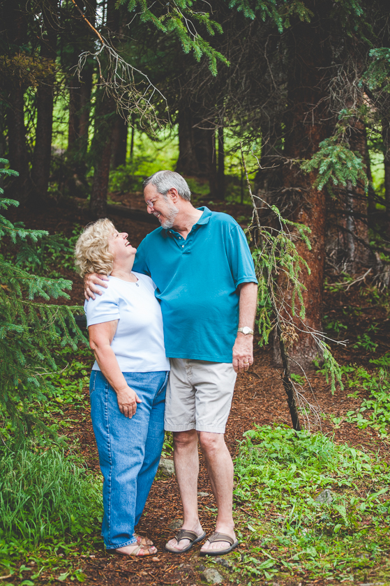 Husband and wife hug in close for a sweet photo during their family portrait session, in the wooded mountains near Breckenridge, Colorado.
