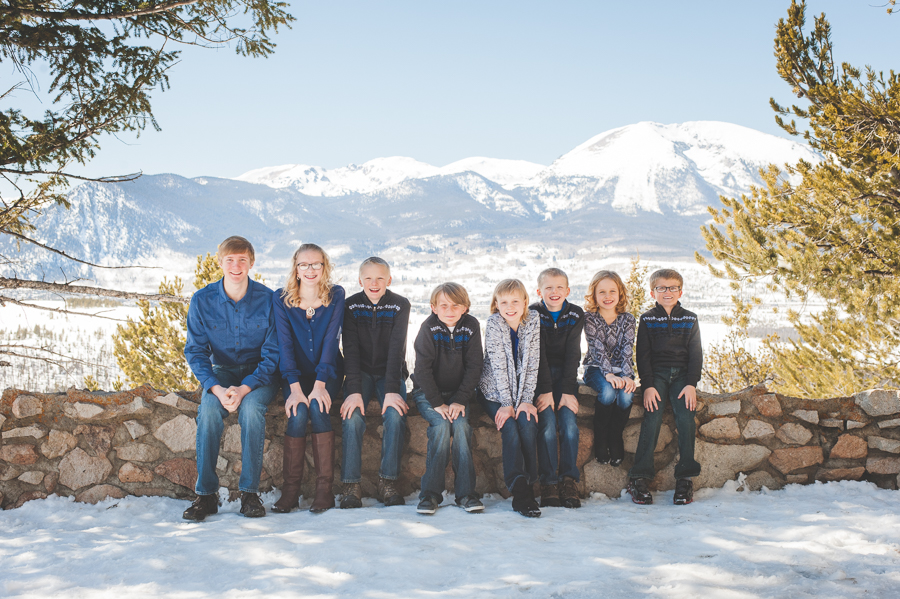 All the grandkids (eight grandchildren, to be exact!) sit side by side on a rock wall at Sapphire Point near Breckenridge, Colorado, overlooking Lake Dillon and Buffalo Mountain, during a winter family photo session.