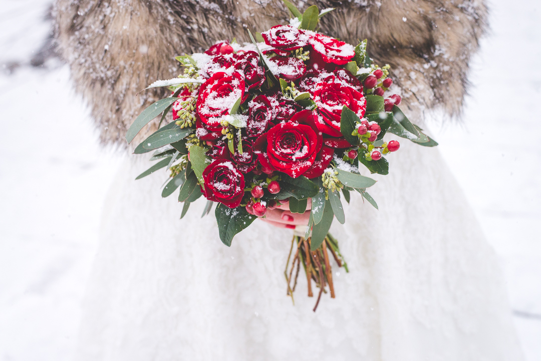 This bride's red accents pop against the falling snow during her winter elopement in Breckenridge, Colorado. | Keeping Composure Photography