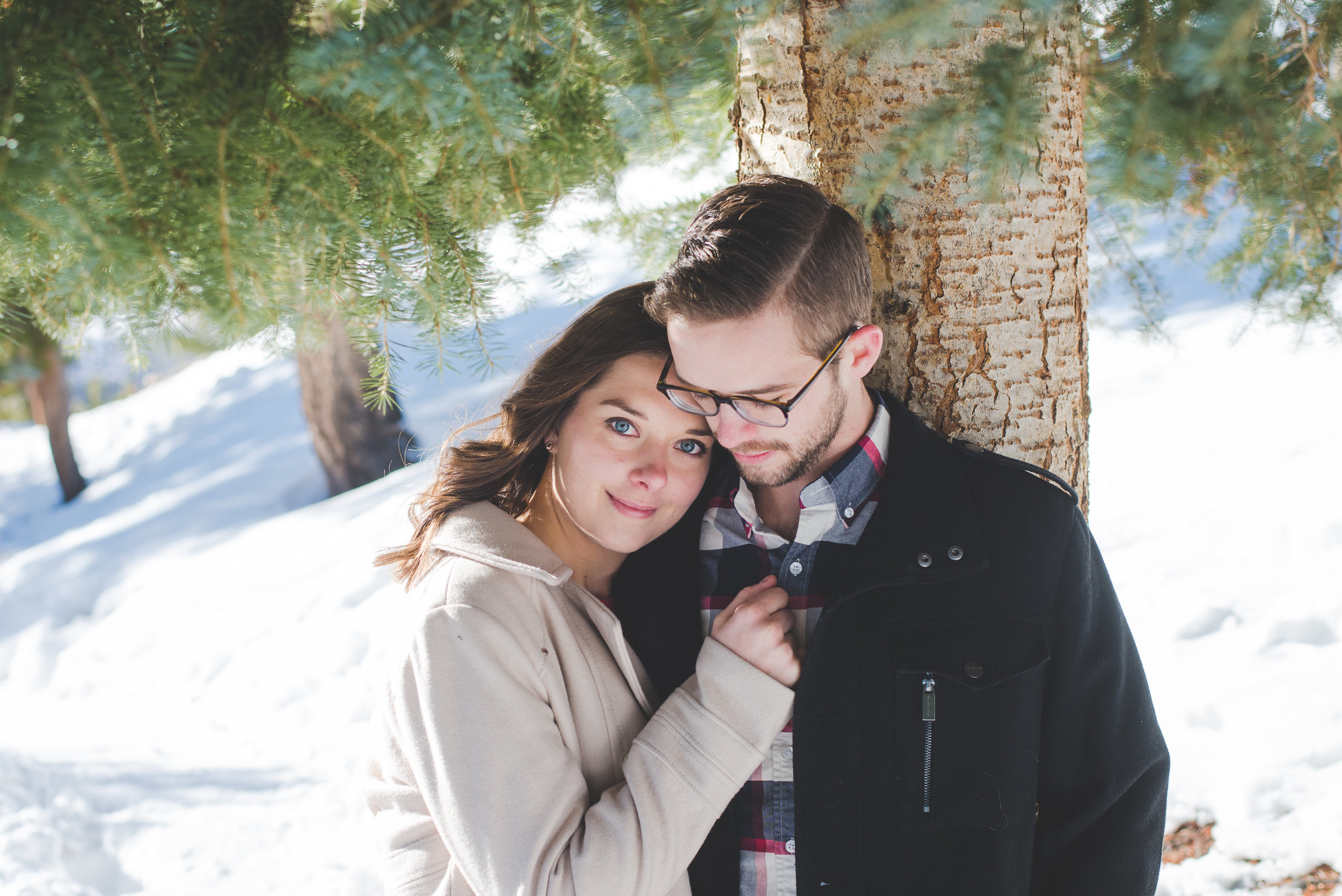 Cuddling together to keep warm during a magical winter engagement shoot in colorado