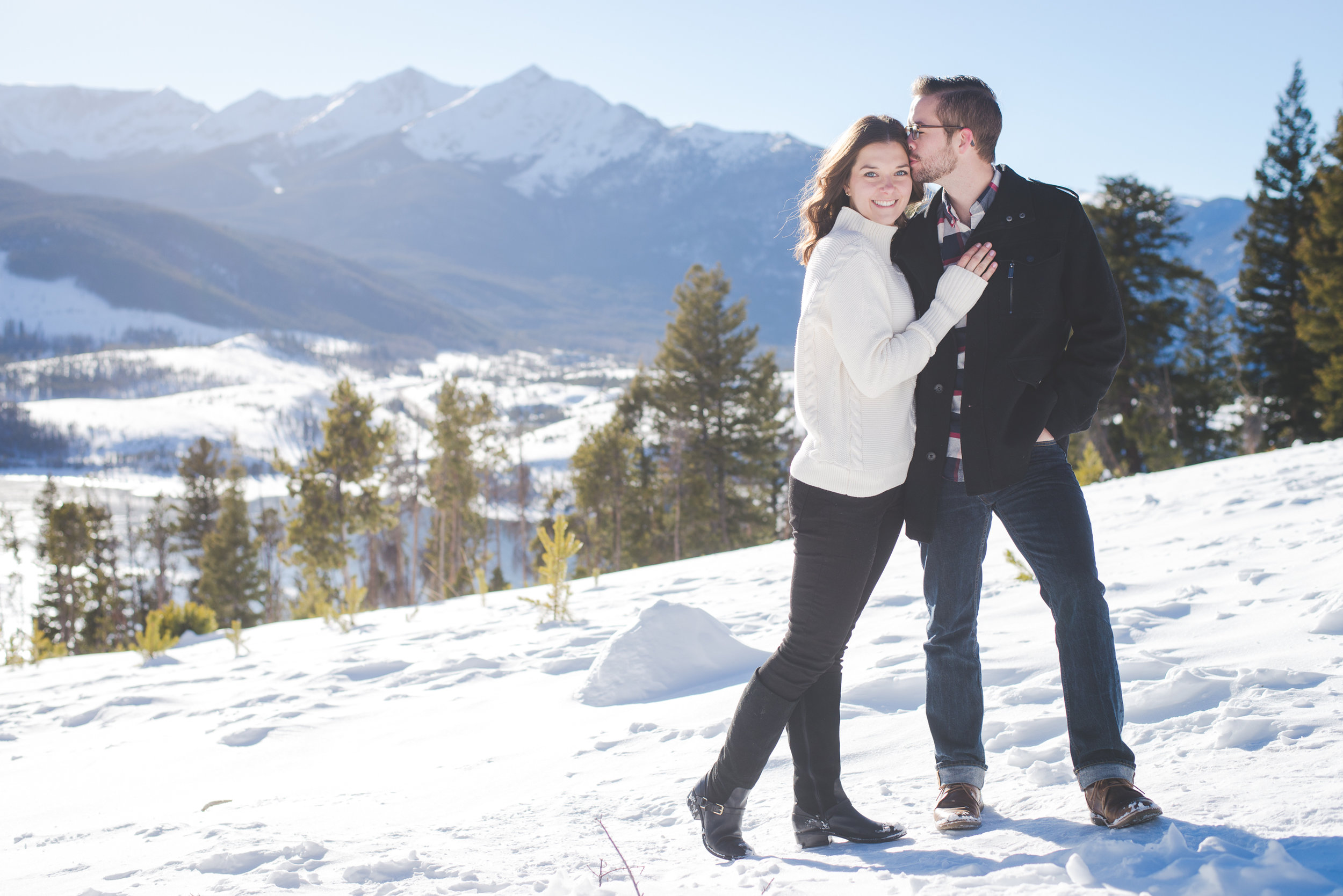 a girl in a cozy white sweater cuddles her new fiance during their winter engagement shoot at sapphire point in colorado