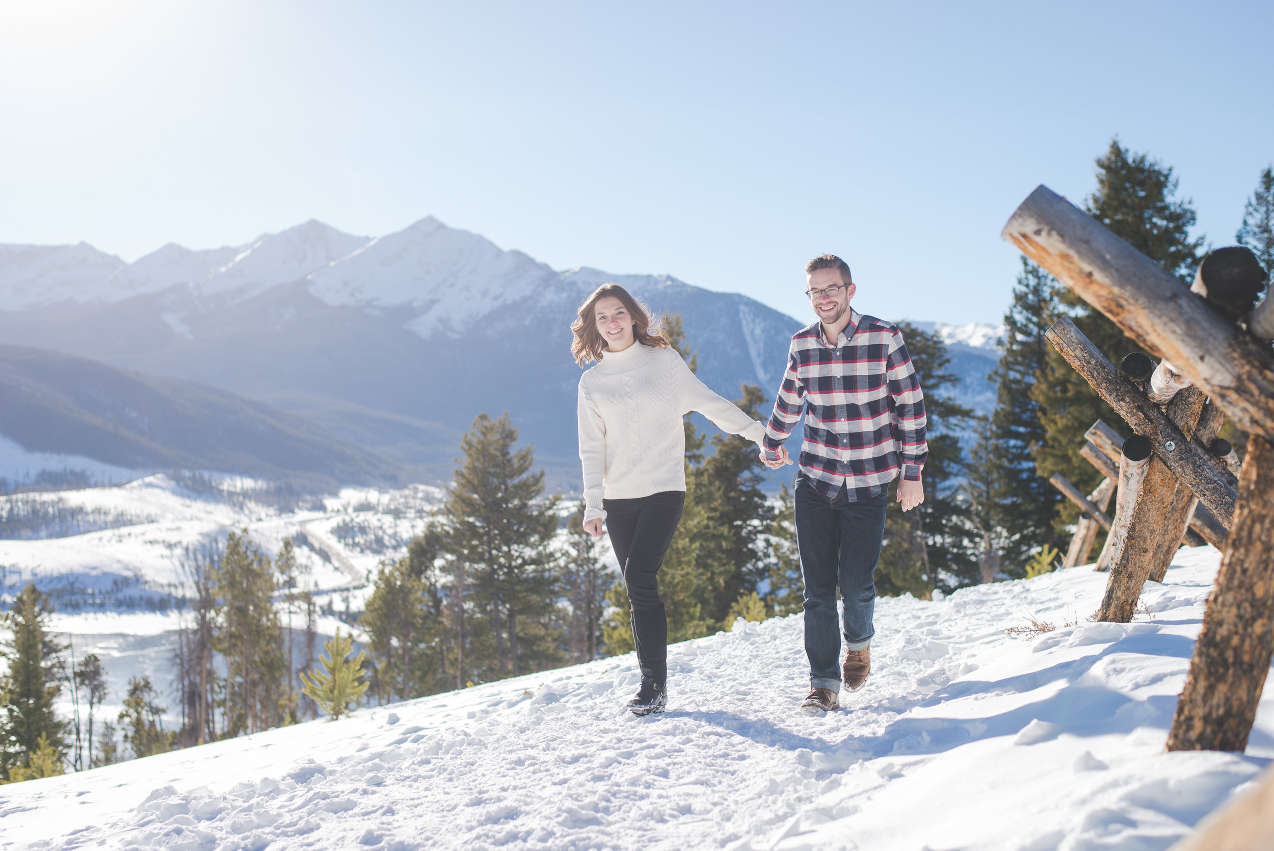 this adorable couple holds hands and walks through the snow, with Peak One in the background during their sapphire point engagement photo session