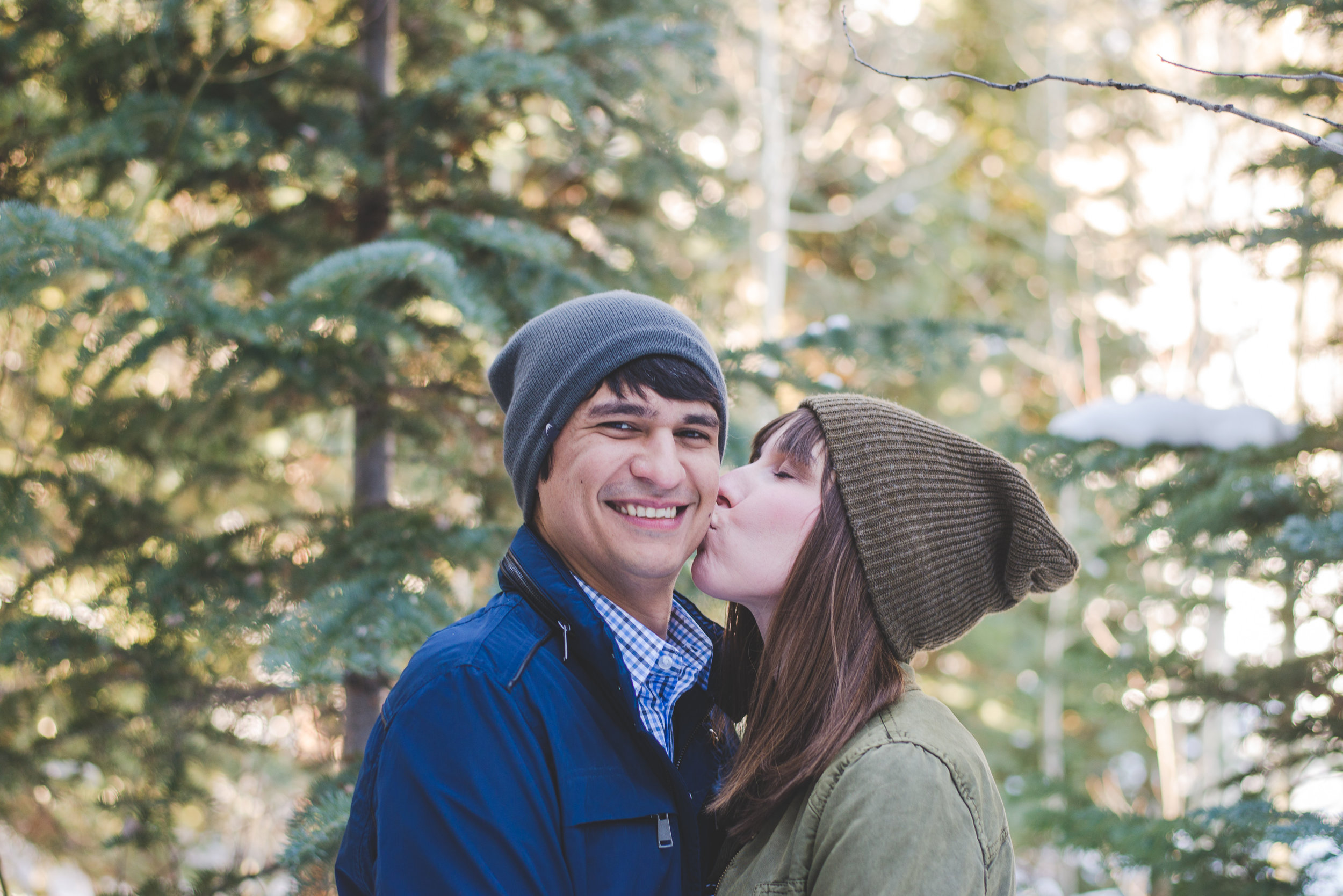beautiful couple sharing some love among the winter pine trees during their family photo shoot in the Colorado mountains!