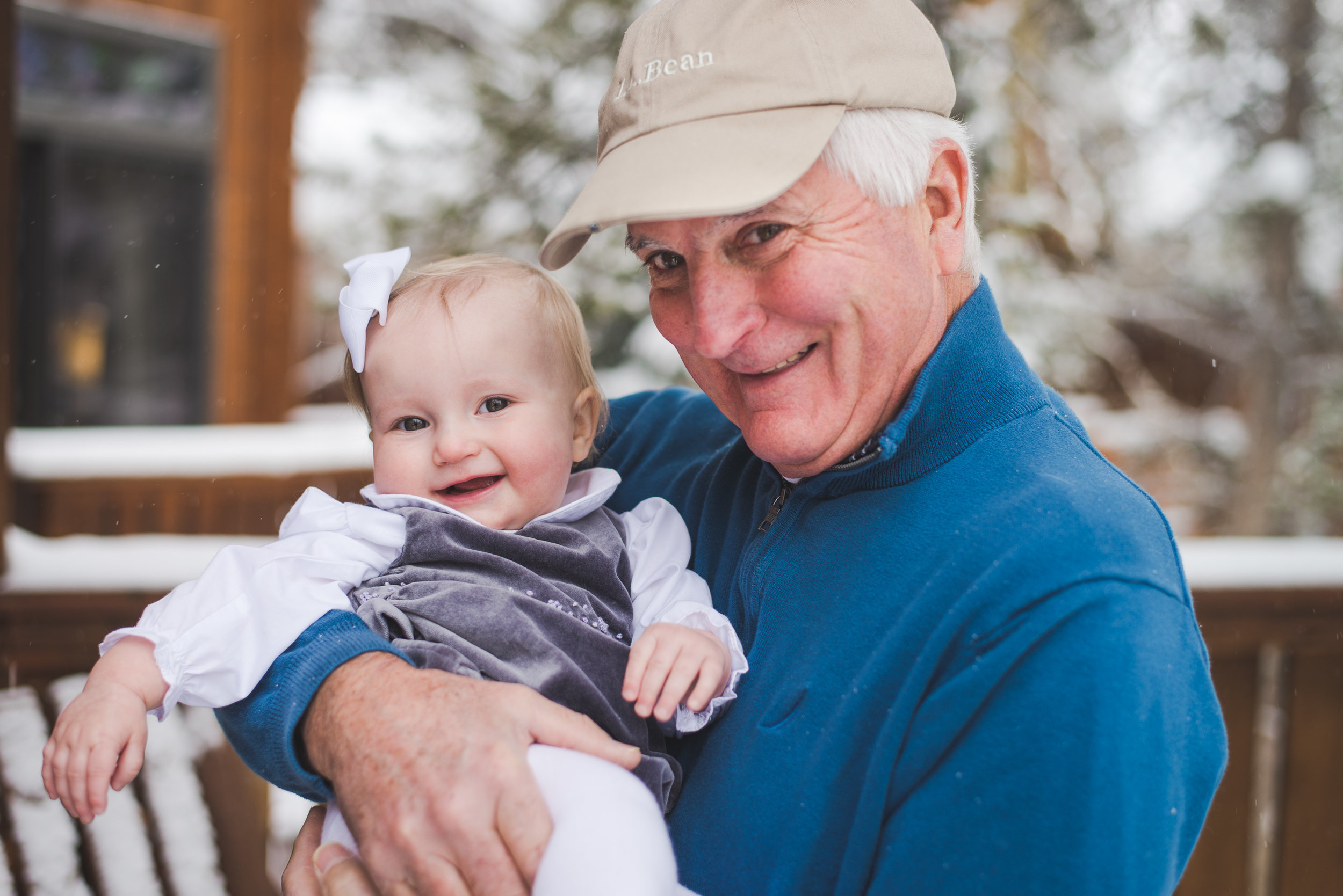 grandpa and his littlest granddaughter pose for an adorable moment during their large winter family photo shoot in Breckenridge, Colorado
